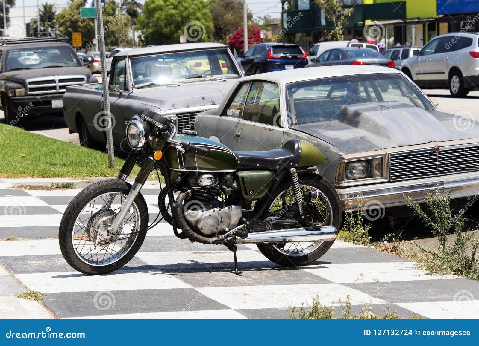 En klassisk motorcykel för tappning och en bil i gatan i Los Angeles, Kalifornien
