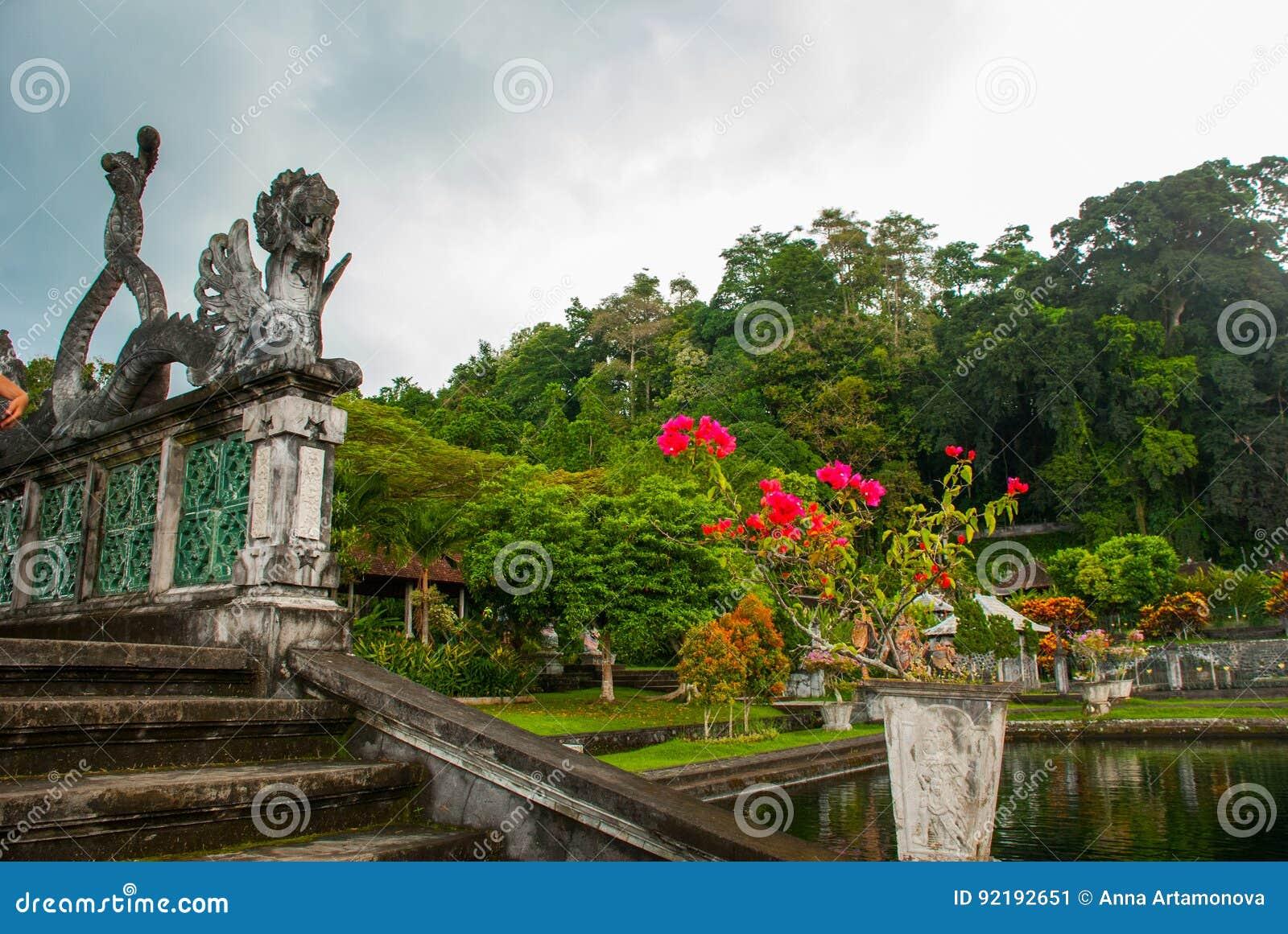 En konstgjord bro med fyra statyer av drakar med vridna svansar, Tirta Gangga parkerar, Karangasem, Bali, Indonesien