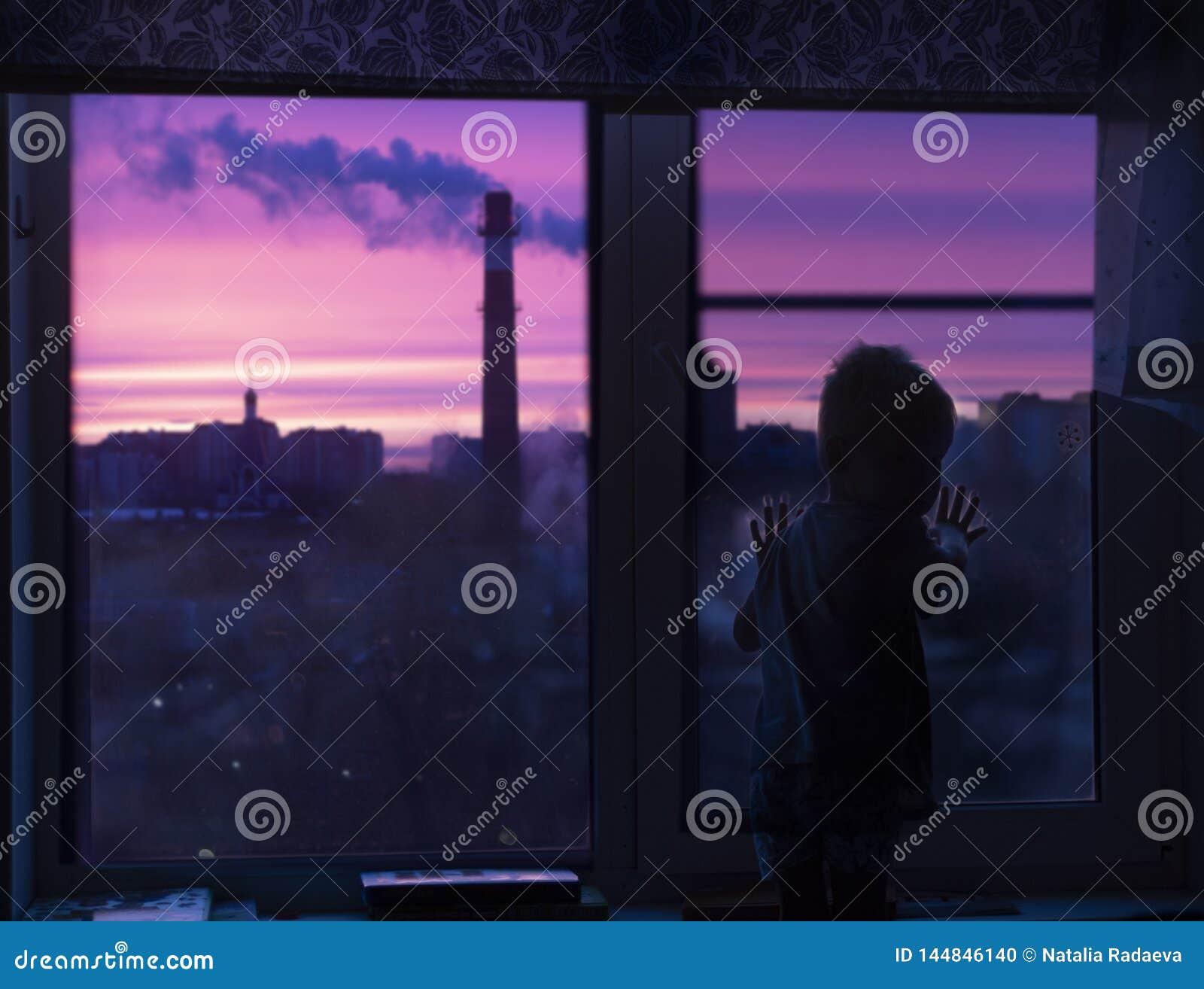 En kontur av ett barnlitet barn på fönstret ser den rosa gryningen och ser rök och stads- hus