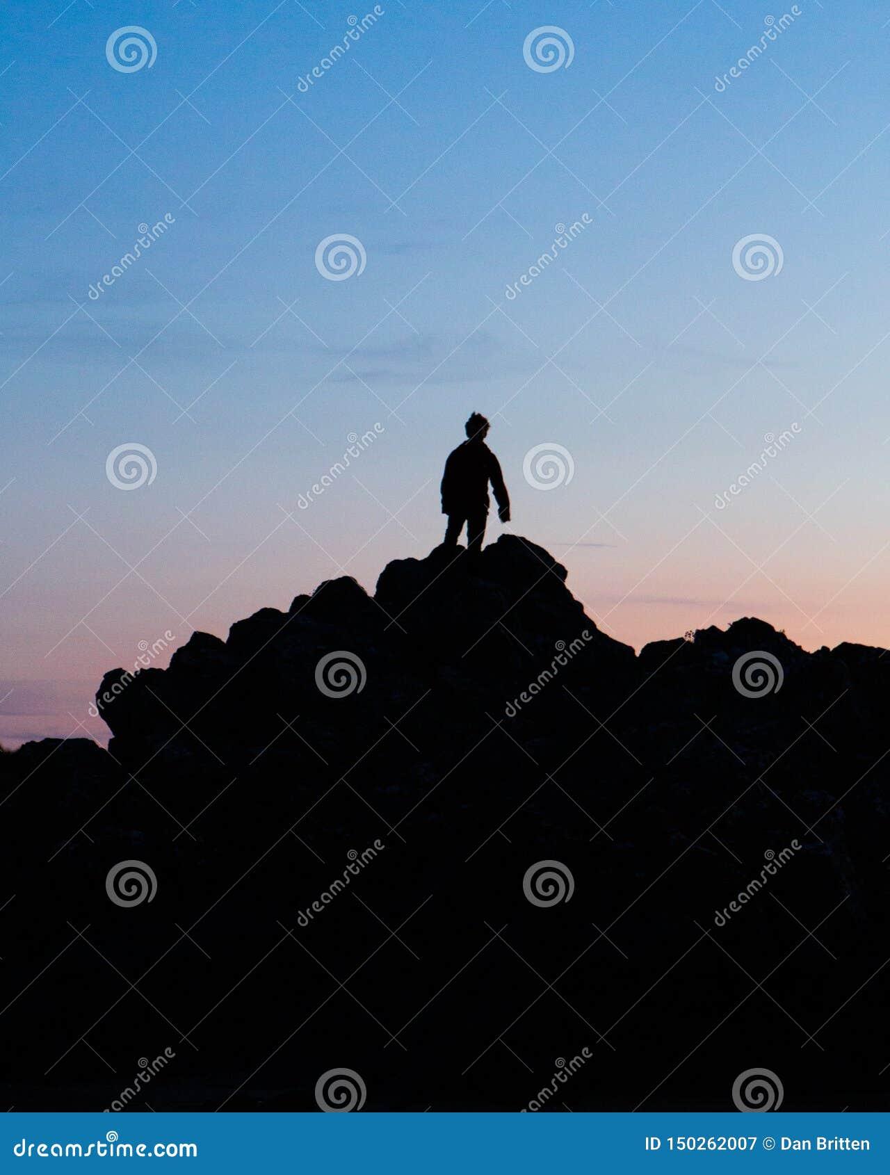 En kontur av en man under en vibrerande solnedgång