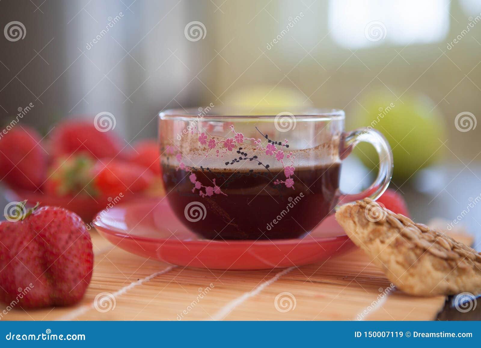 En kopp av härligt svart engelskt te för frukost med jordgubbar och kakor