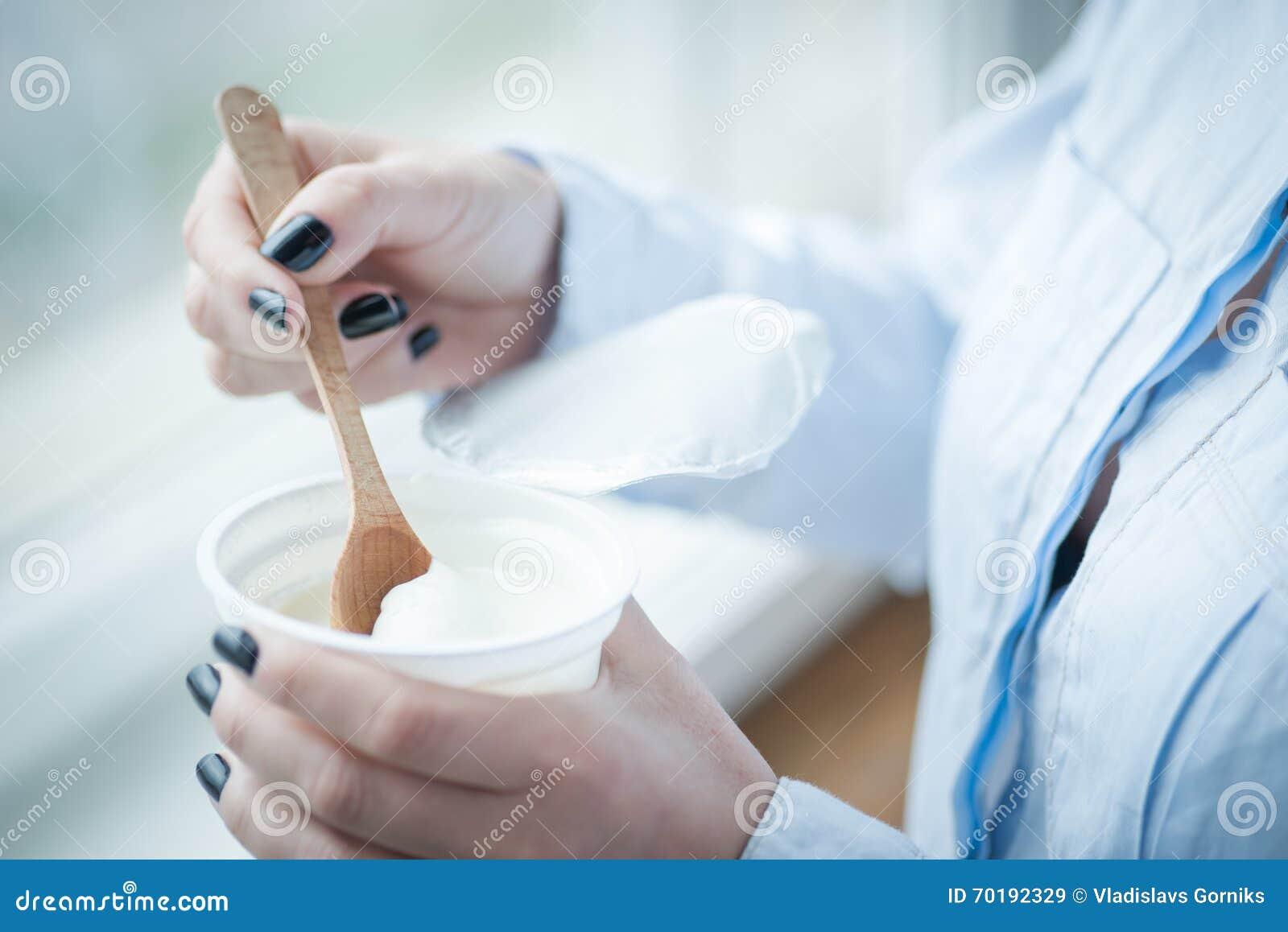En kopp av ny yoghurt i kvinnas händer