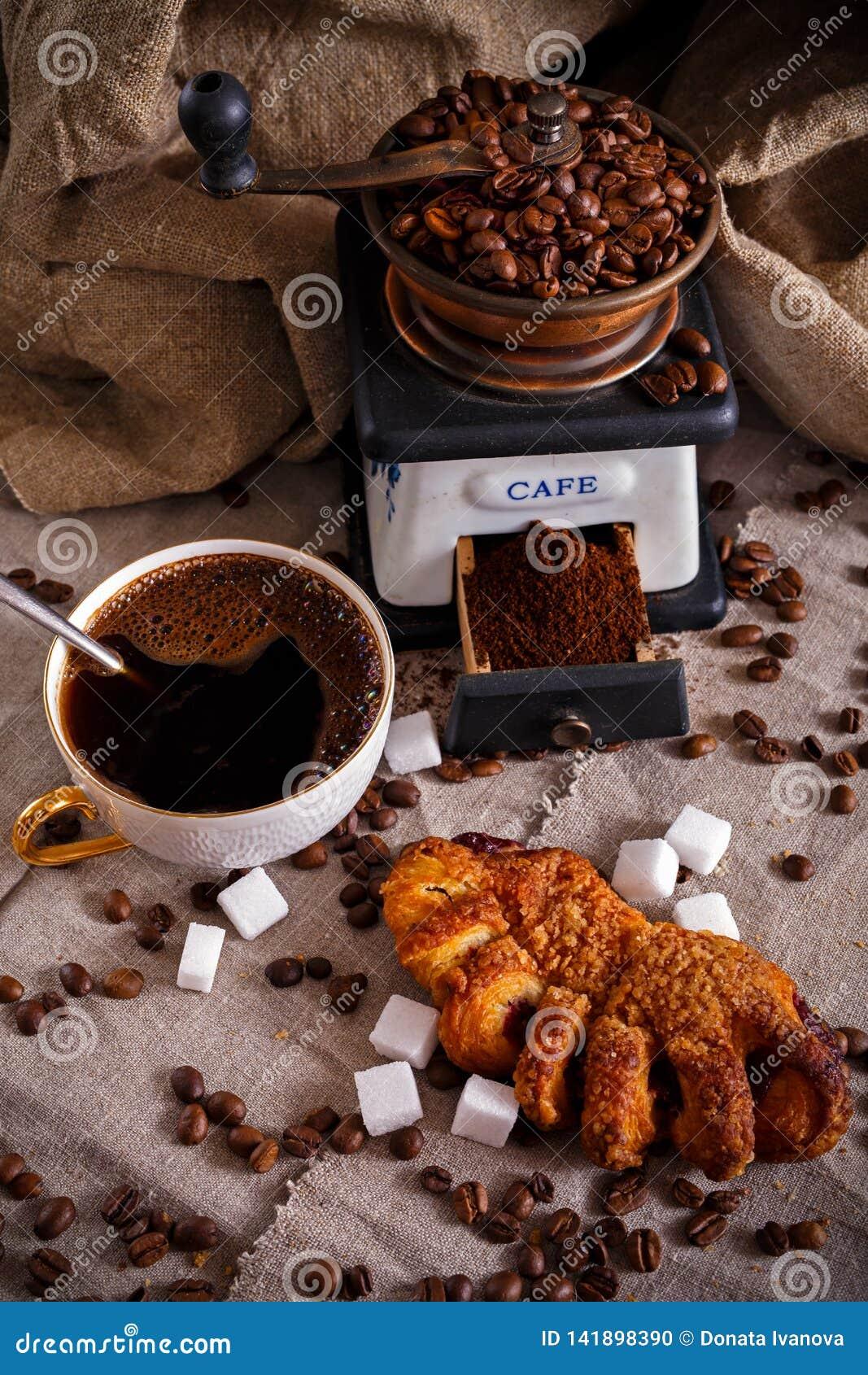 En kopp av svart kaffe med en kringla, ett kaffe maler och spridda kaffebönor på en tabell som täckas med säckväv
