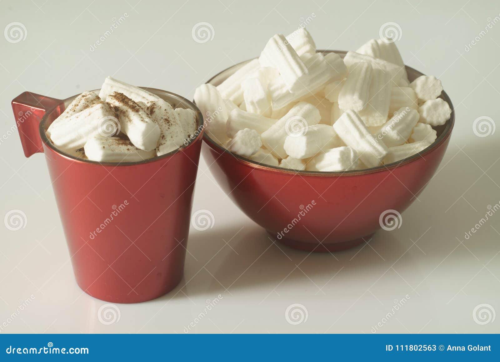 En kopp kaffe eller en varm choklad med marshmallower och en röd platta på en vit bakgrund close upp behandla som ett barn fotoet