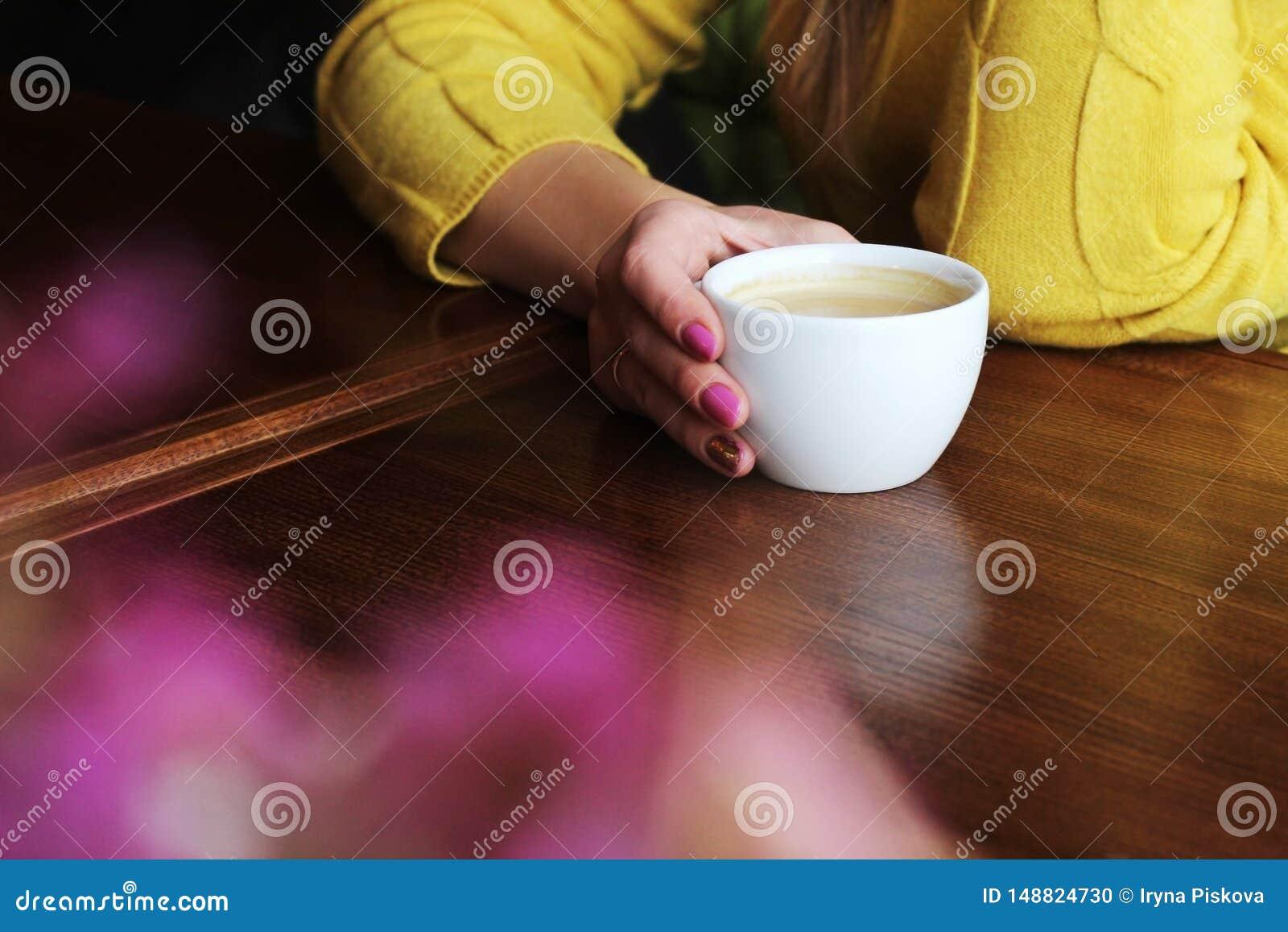 En kopp kaffe i händerna av en flicka