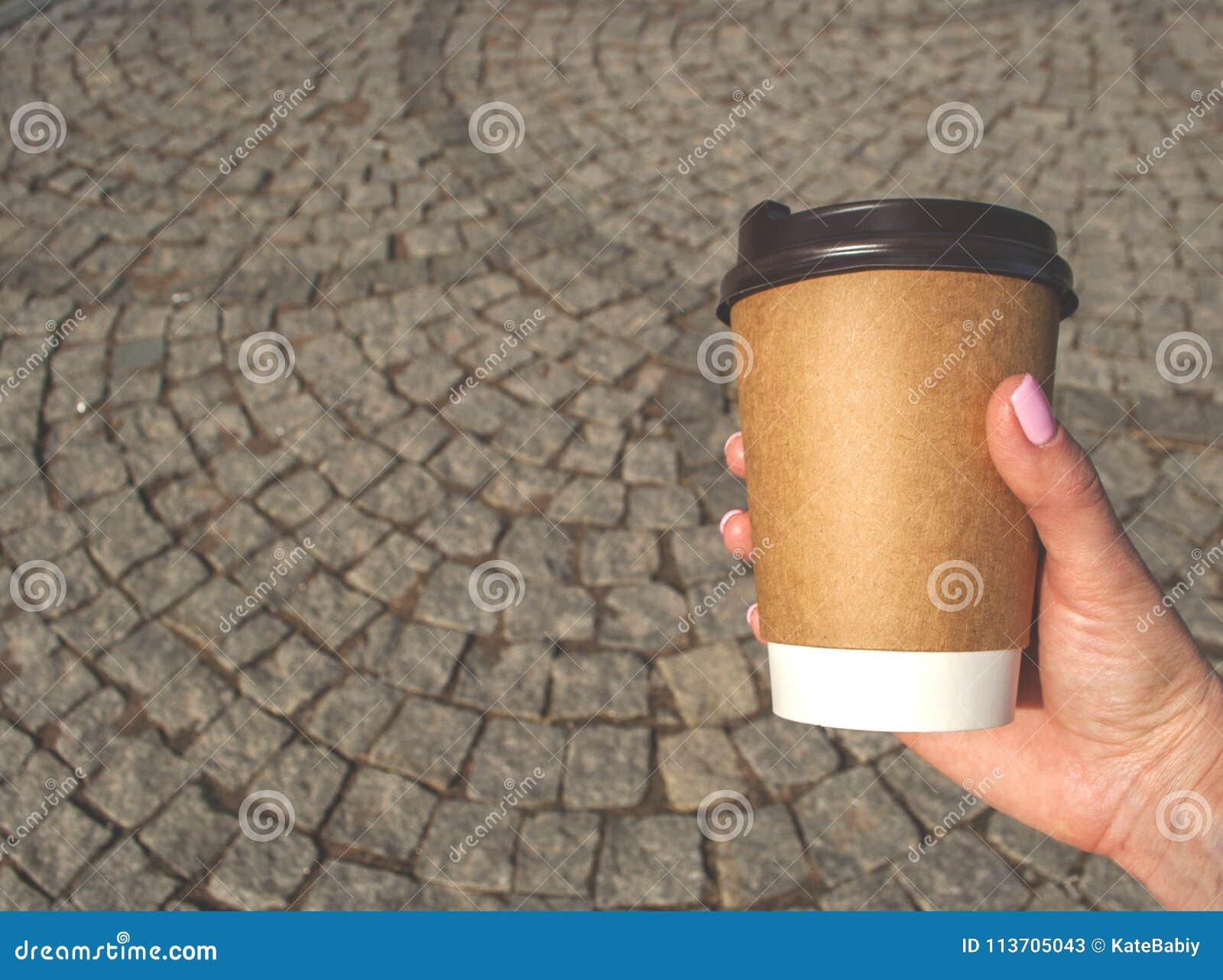 En kopp kaffe i en hand för kvinna` s