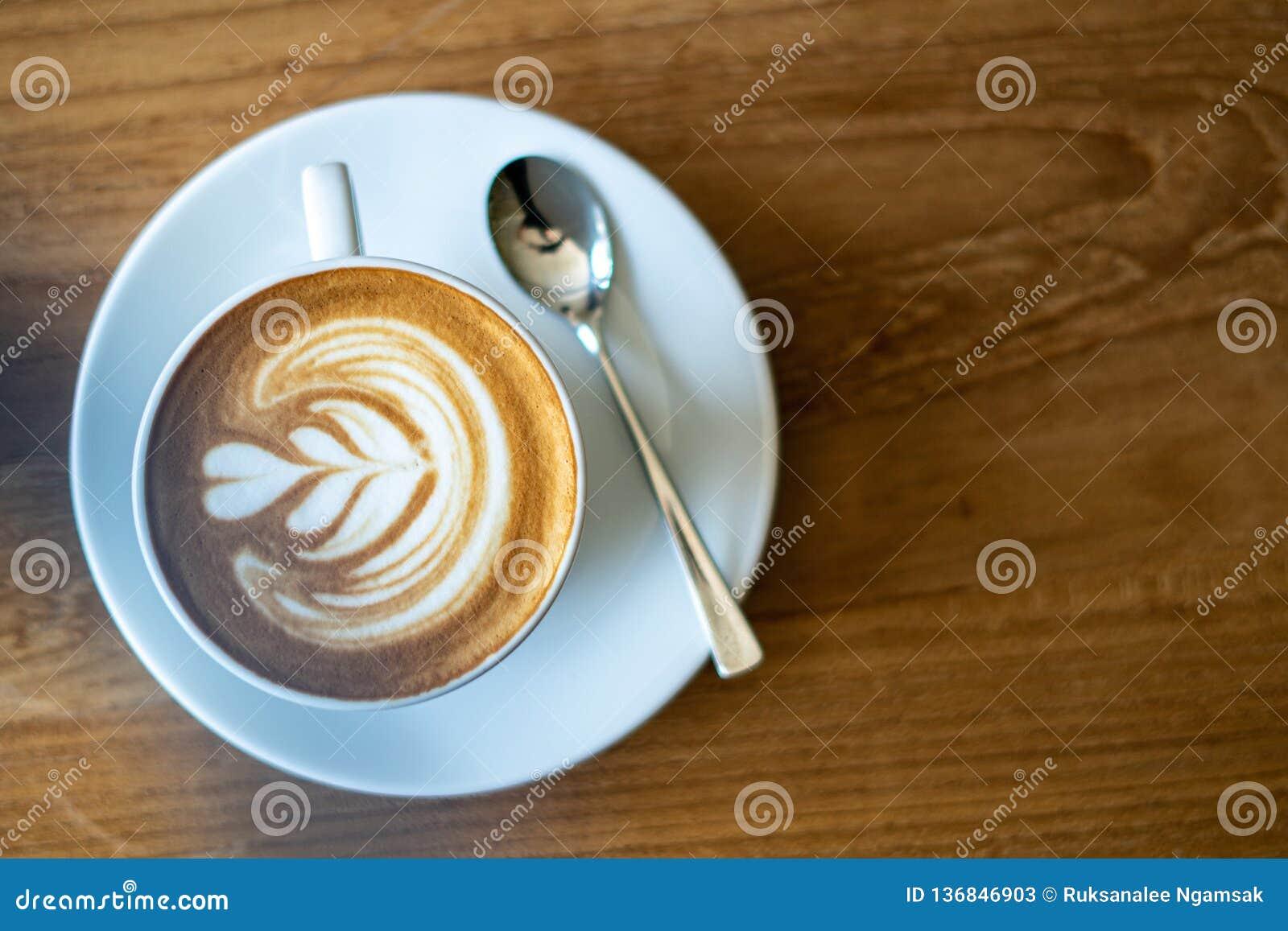 En kopp kaffe på den gamla trätabellen i kafékaffeavbrott i morgon