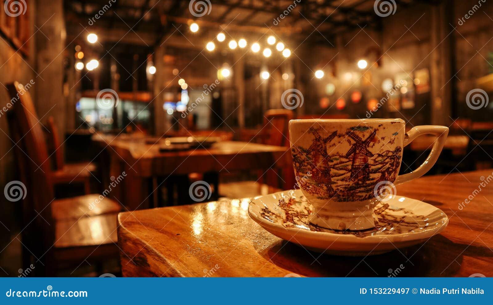 En kopp kaffe tjänade som på en trätabell med en lugna atmosfärcoffee shop