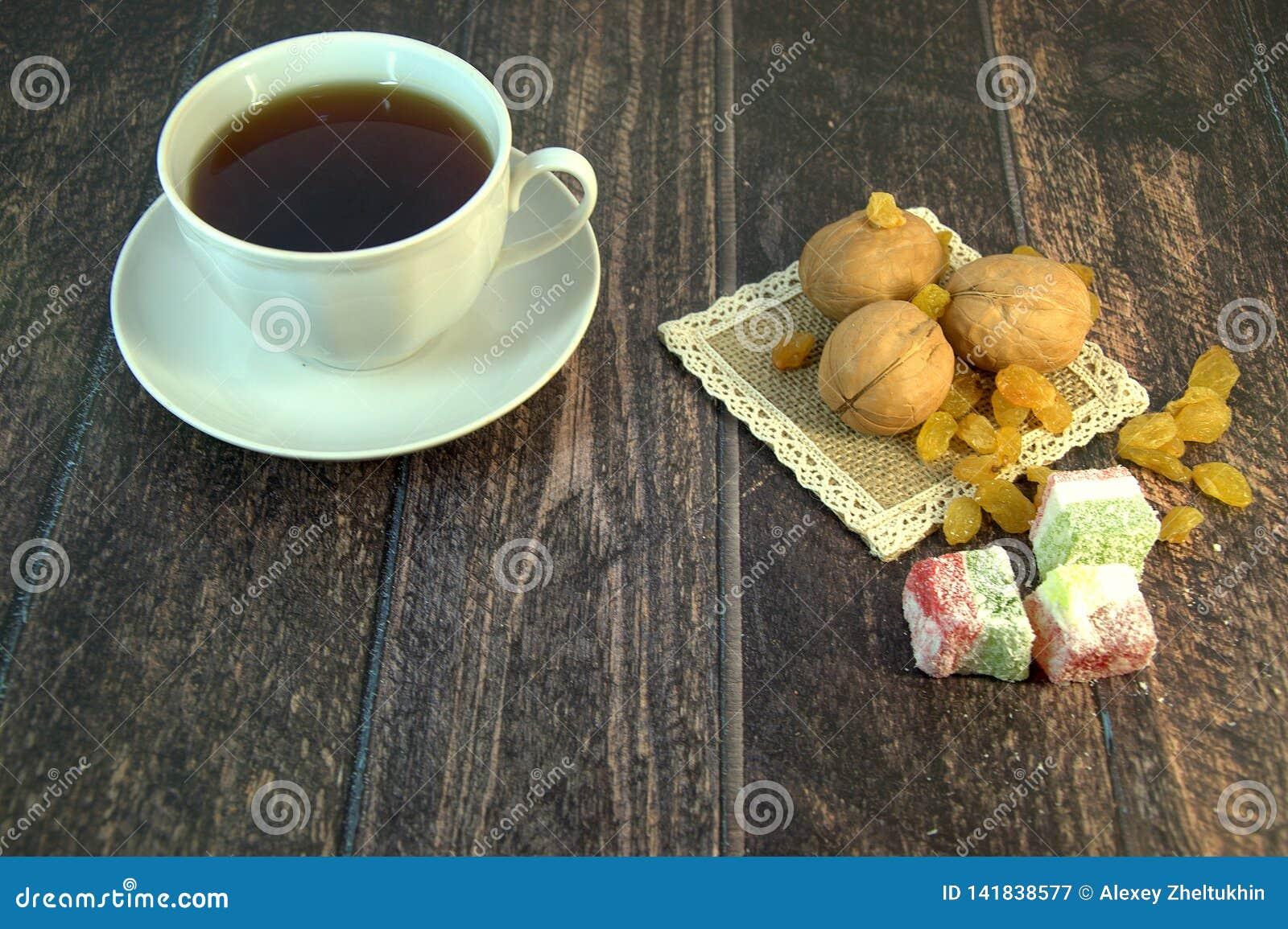 En kopp te på ett tefat, tre valnötter, vita russin och turkisk fröjd på en textilservett, lögn på en trätabell 1 livstid fortfar