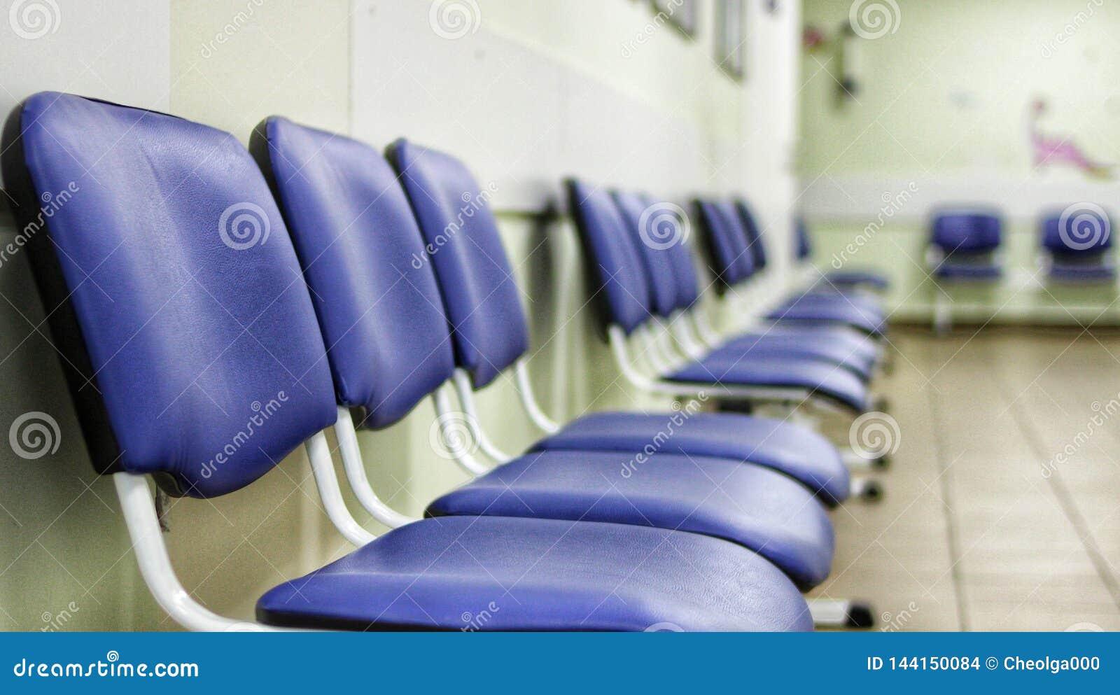 En korridor i ett sjukhus, stolar för patienter som väntar för att se en doktor, rader av blåa stolar