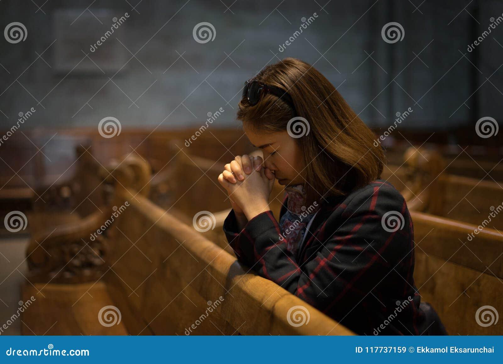 En kristen flicka är sitta och be med bruten hjärta i