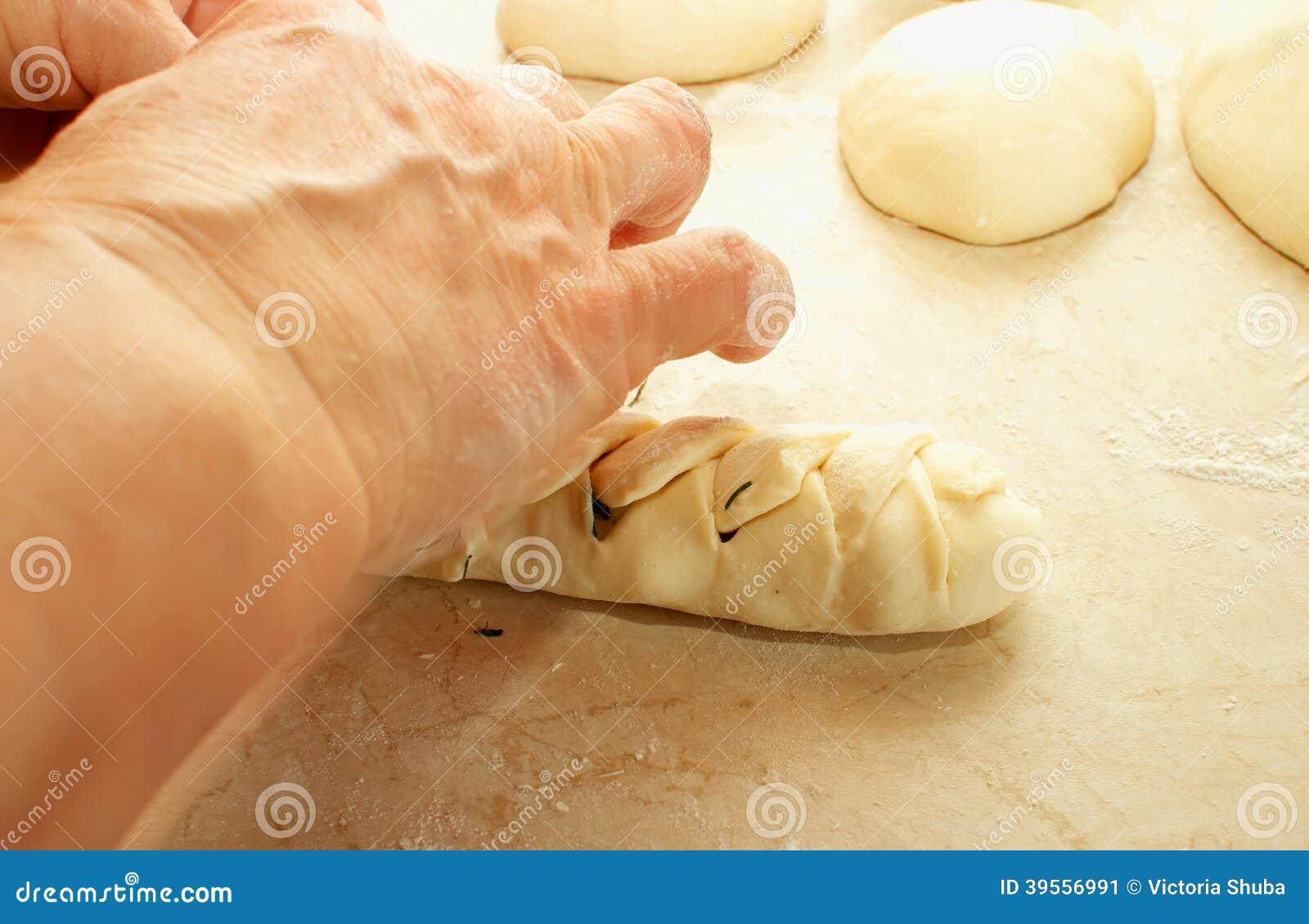 En kvinna förbereder en hamburgare som flätade trådar av deg