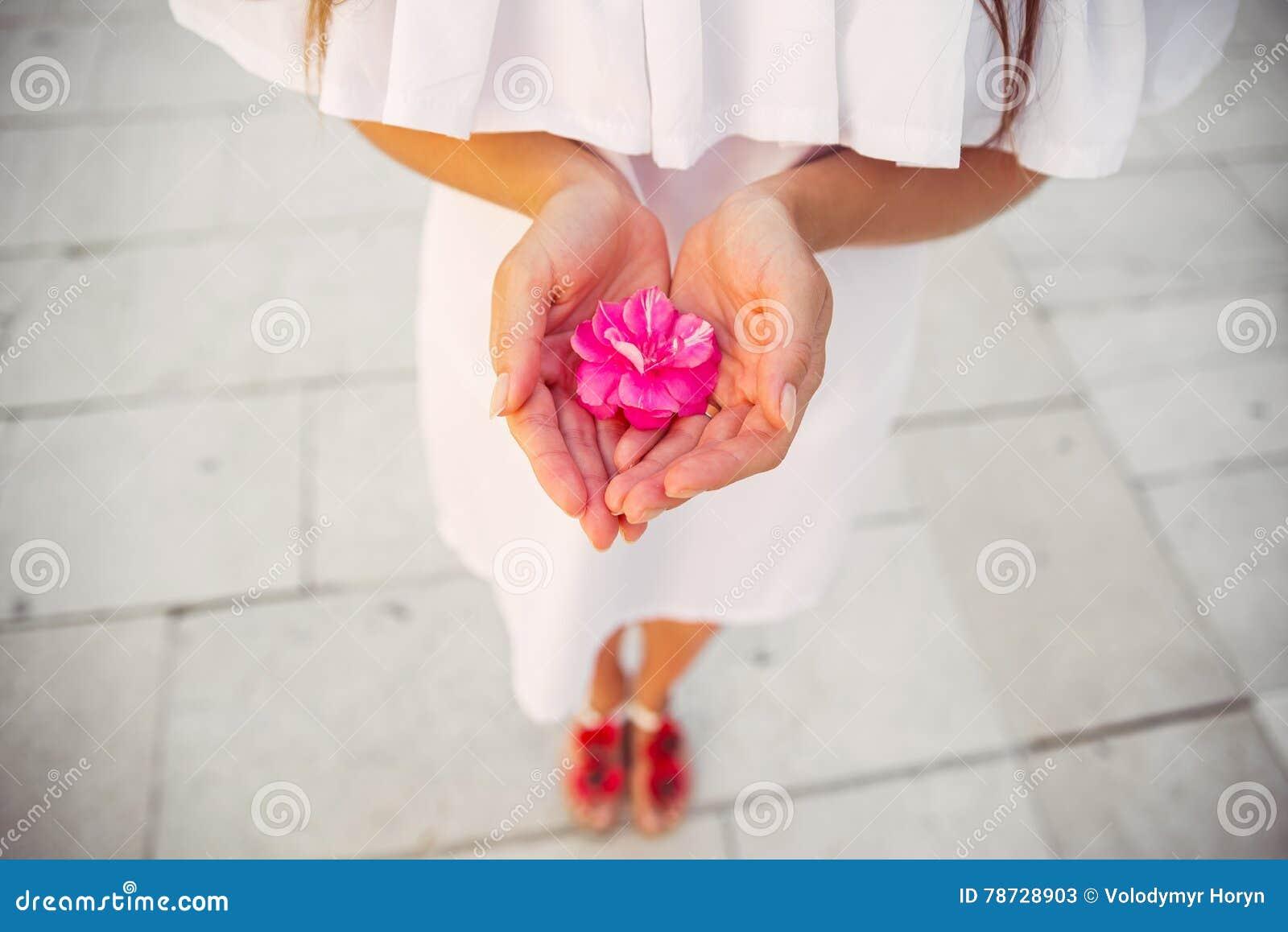 En kvinna i en vit klänning som rymmer en blomma