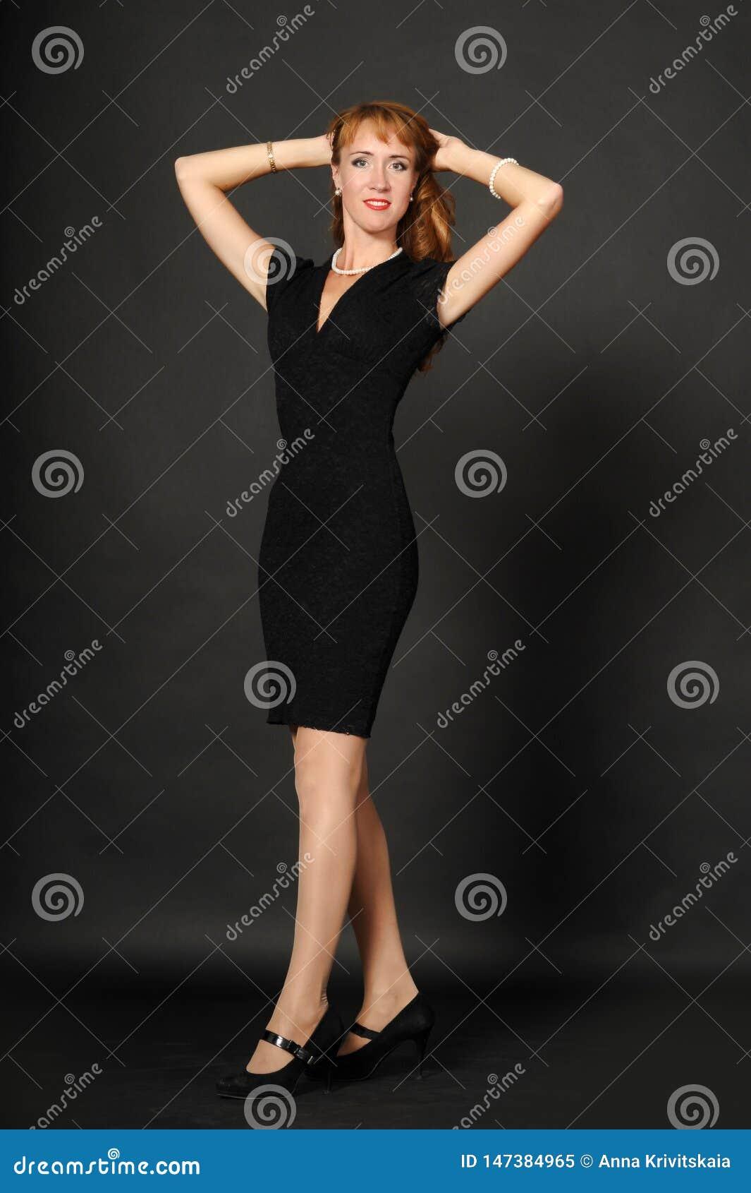 En kvinna i en svart klänning som rymmer hennes hår