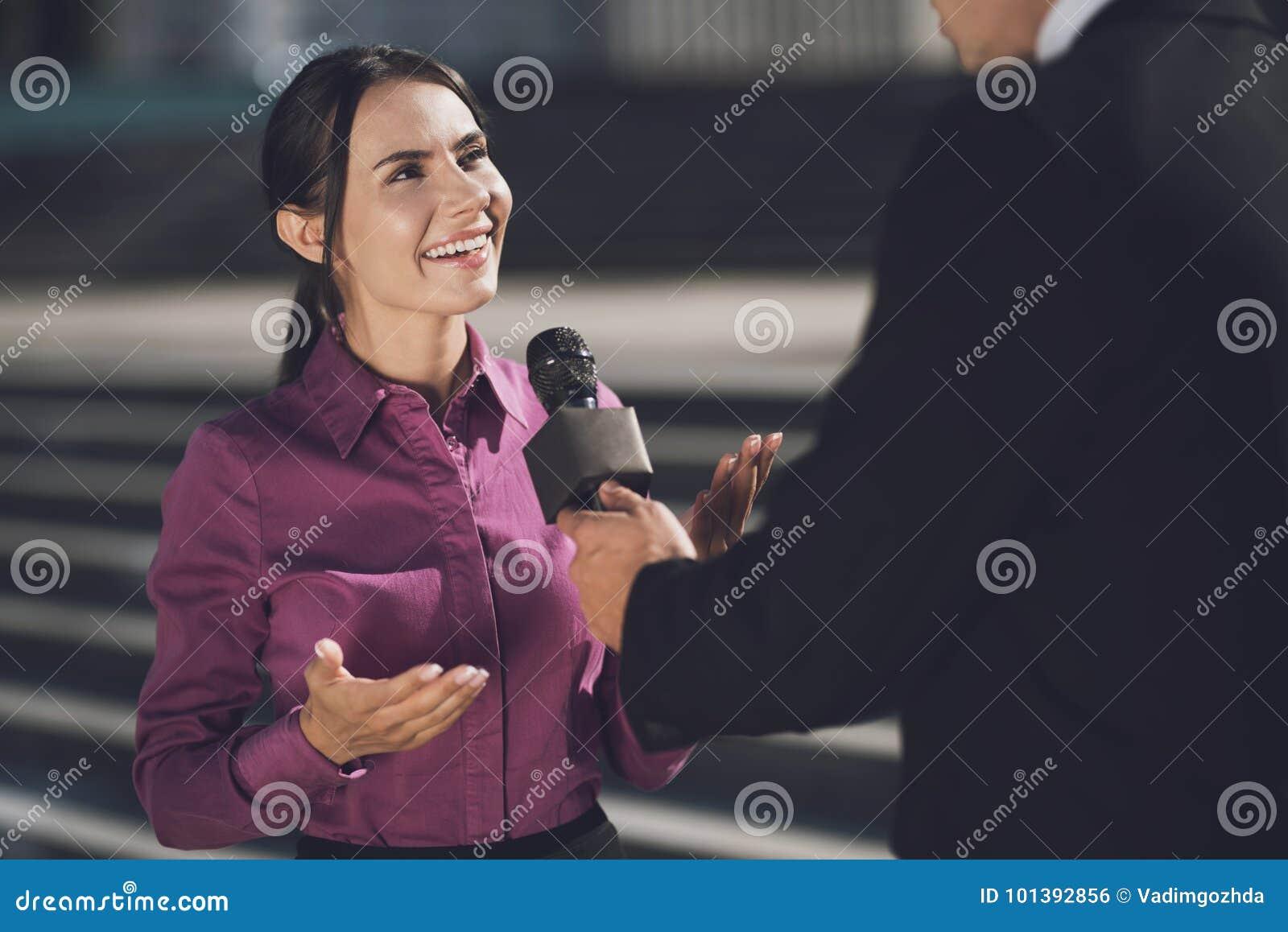 En kvinna med ett leende på hennes framsida svarar frågan En man rymmer en mikrofon som lyssnar till ett svar