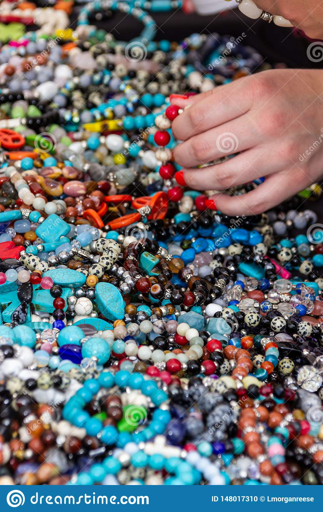 En kvinna med fingernaglar smärtade röda håll ett armband med röda pärlor