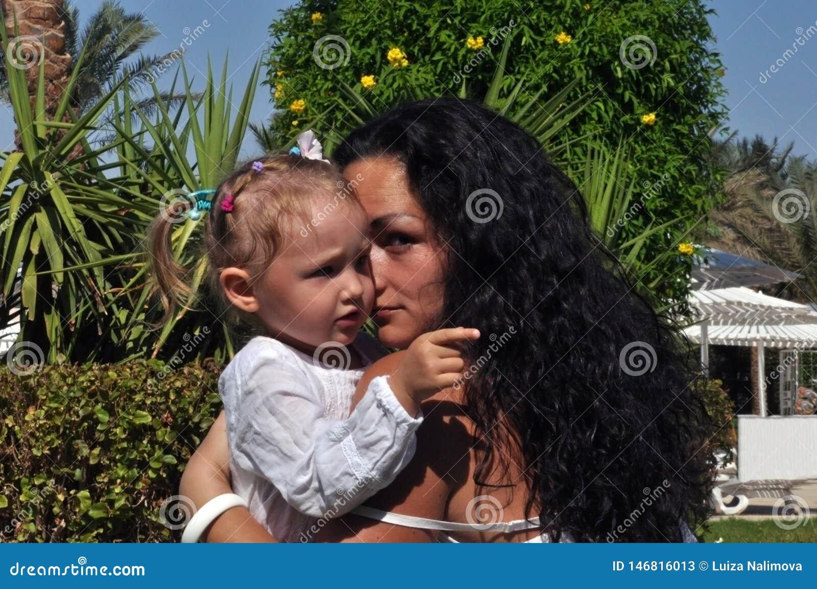En kvinna med långt svart lockigt hår omfamnar hennes dotter på en solig dag