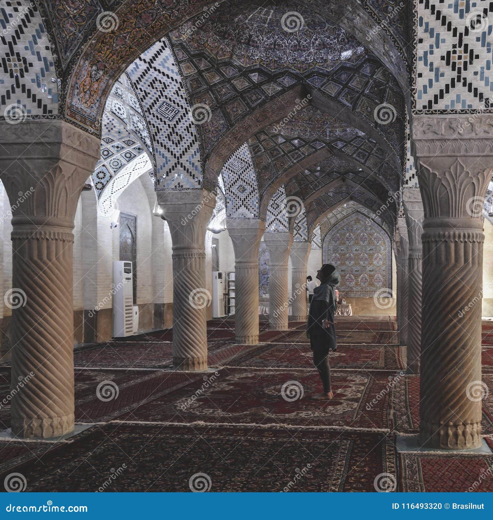 En kvinna med en sjalett ber på Nasir Al-Mulk Mosque i Shiraz, Iran, också som är bekant som rosa moské