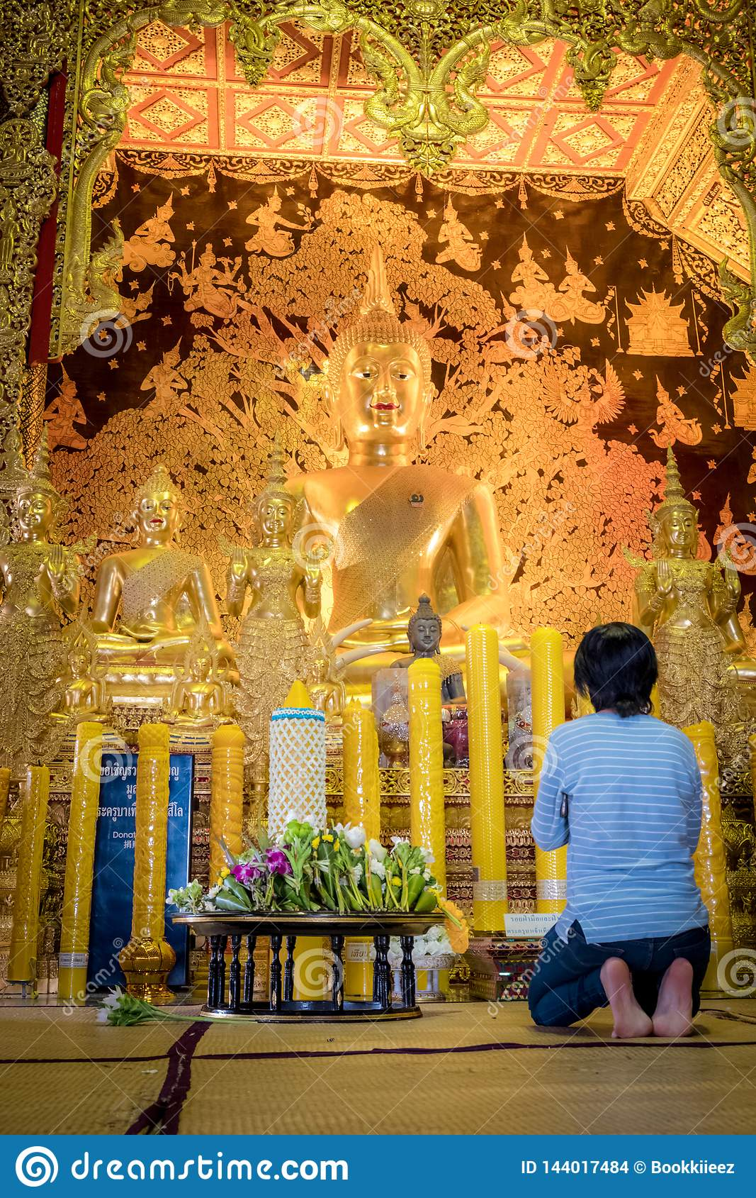En kvinna sitter f?r att be framme av den guld- Buddhastatyn av Thailand templet namngav ?Wat Den Salee Sri Muang Gan Wat Ban Den