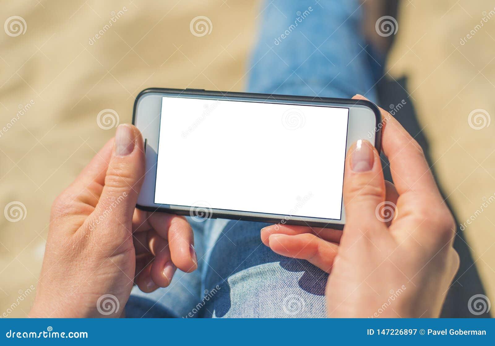 En kvinna som rymmer en vit mobiltelefon med en tom sk?rm