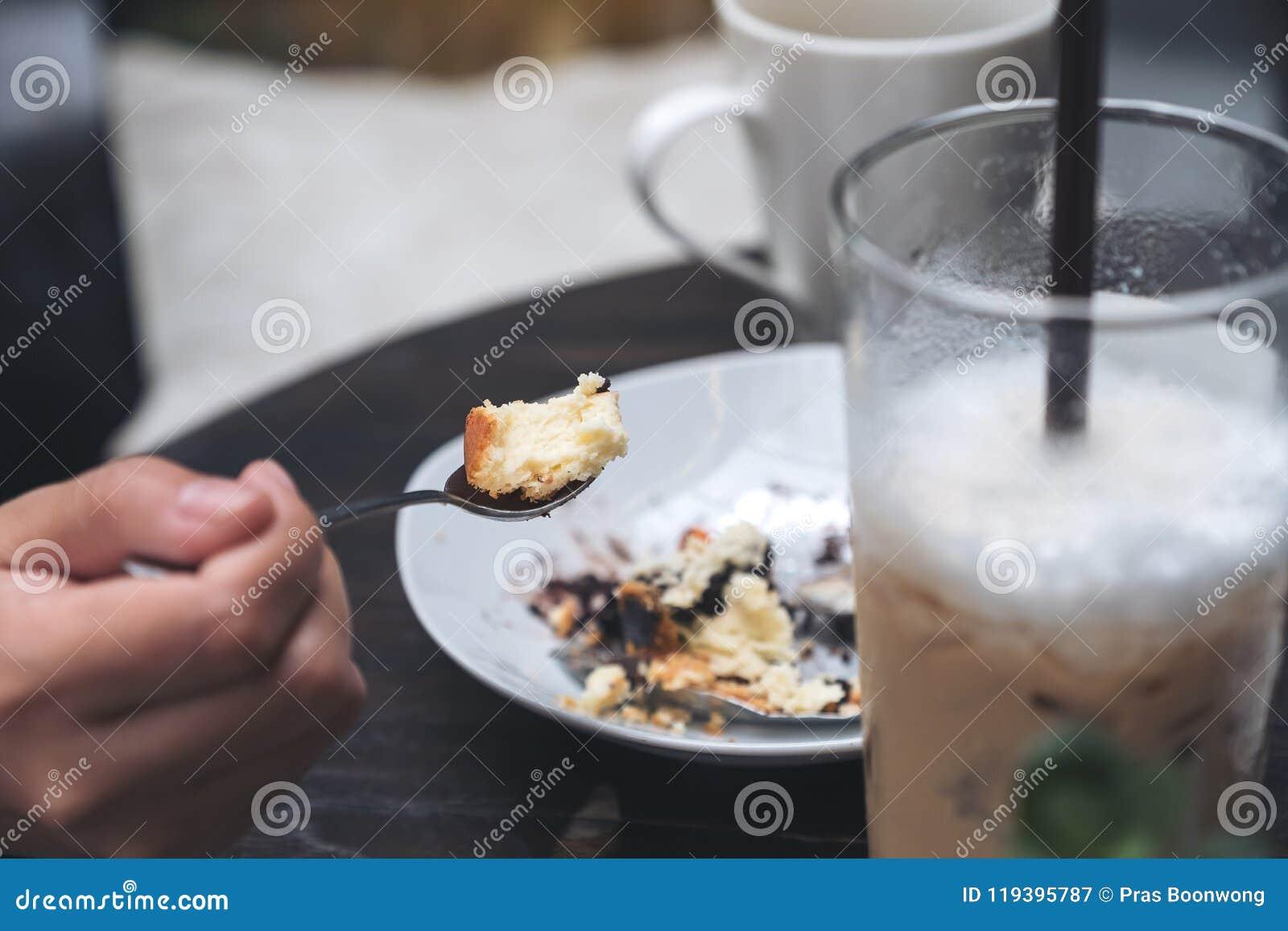 En kvinna tycker om att äta ostkaka och kaffe i kafé