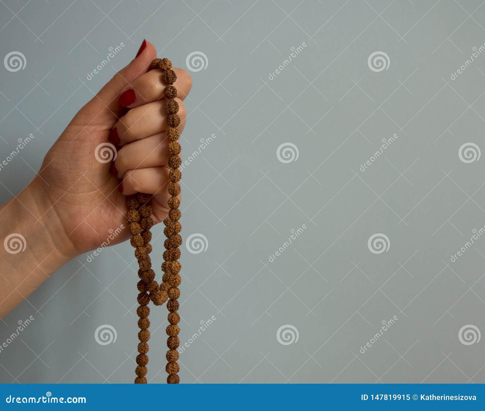 En kvinnas hande som rymmer rudrakshap?rlradbandet p? den bl?a bakgrunden med kopieringsutrymme