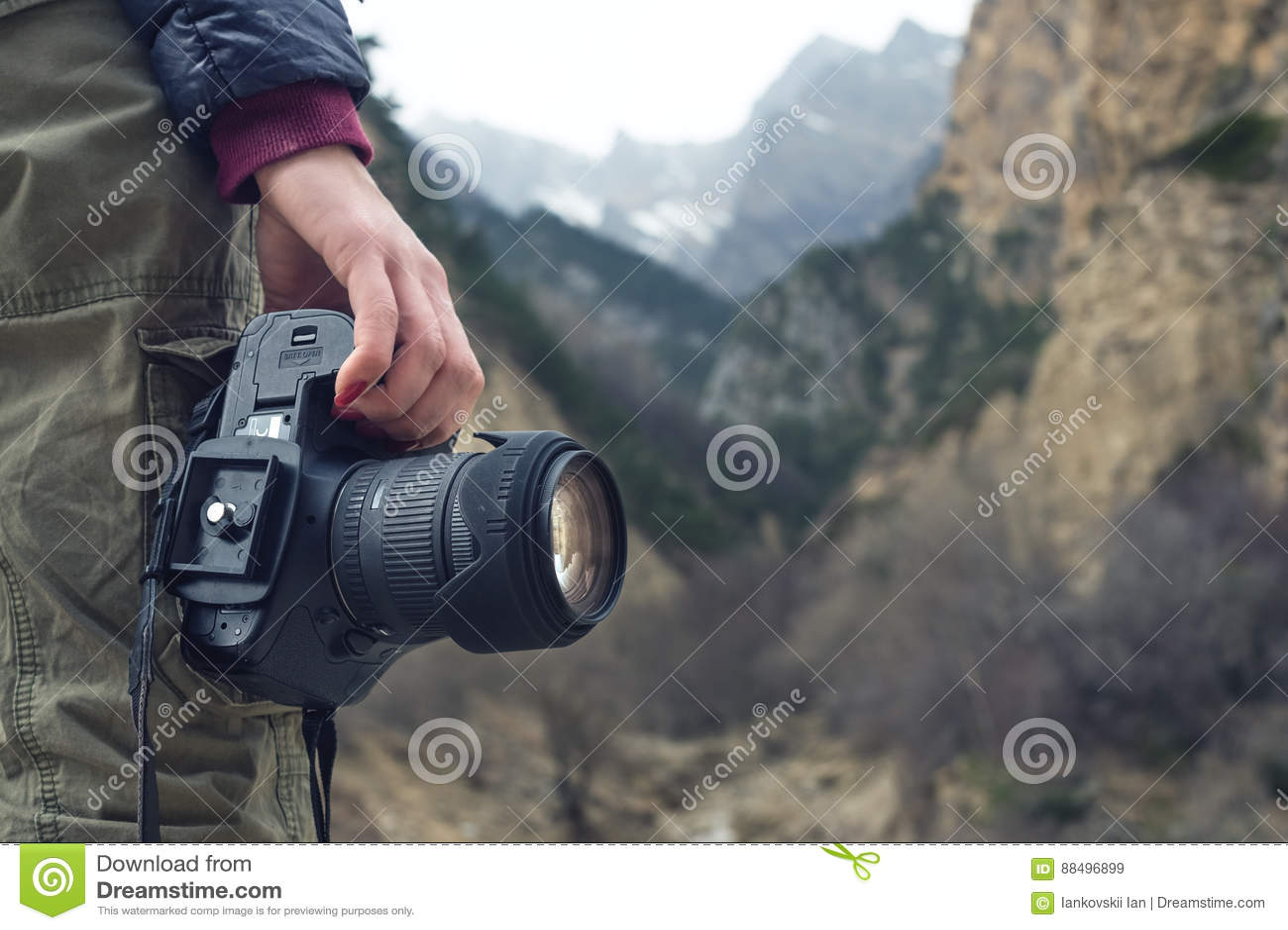 En kvinnlig hand rymmer en kamera mot ett berglandskap