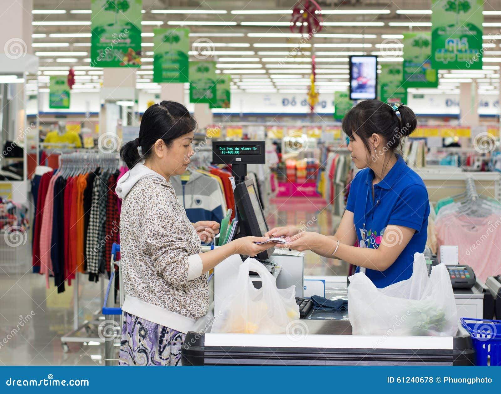 En kvinnlig kassörska av den Coopmart supermarket