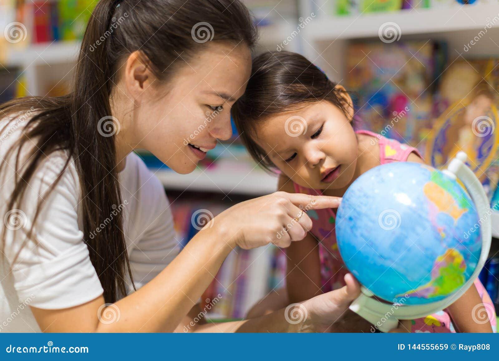En lärare och en förskole- student som lär geografi på ett världsjordklot
