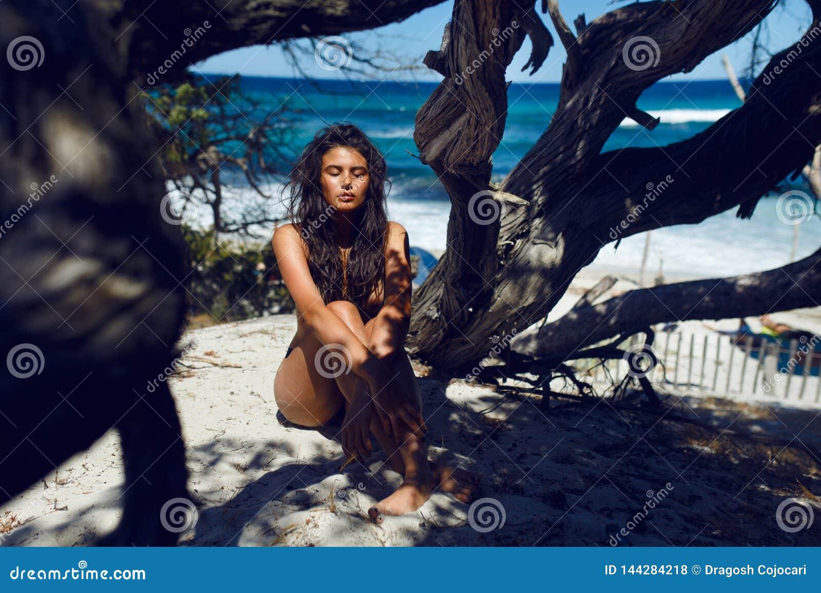 En lång hårkvinnlig för härlig brunett som placerar på stranden med stängda ögon blåa hav vågor av för den Korsika ön,