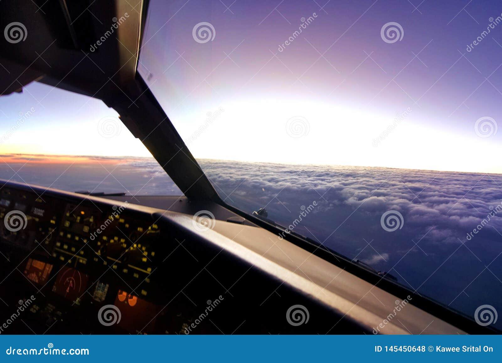 En la opinión de la carlinga del aeroplano, vuelo del aeroplano sobre la nube durante puesta del sol por la tarde