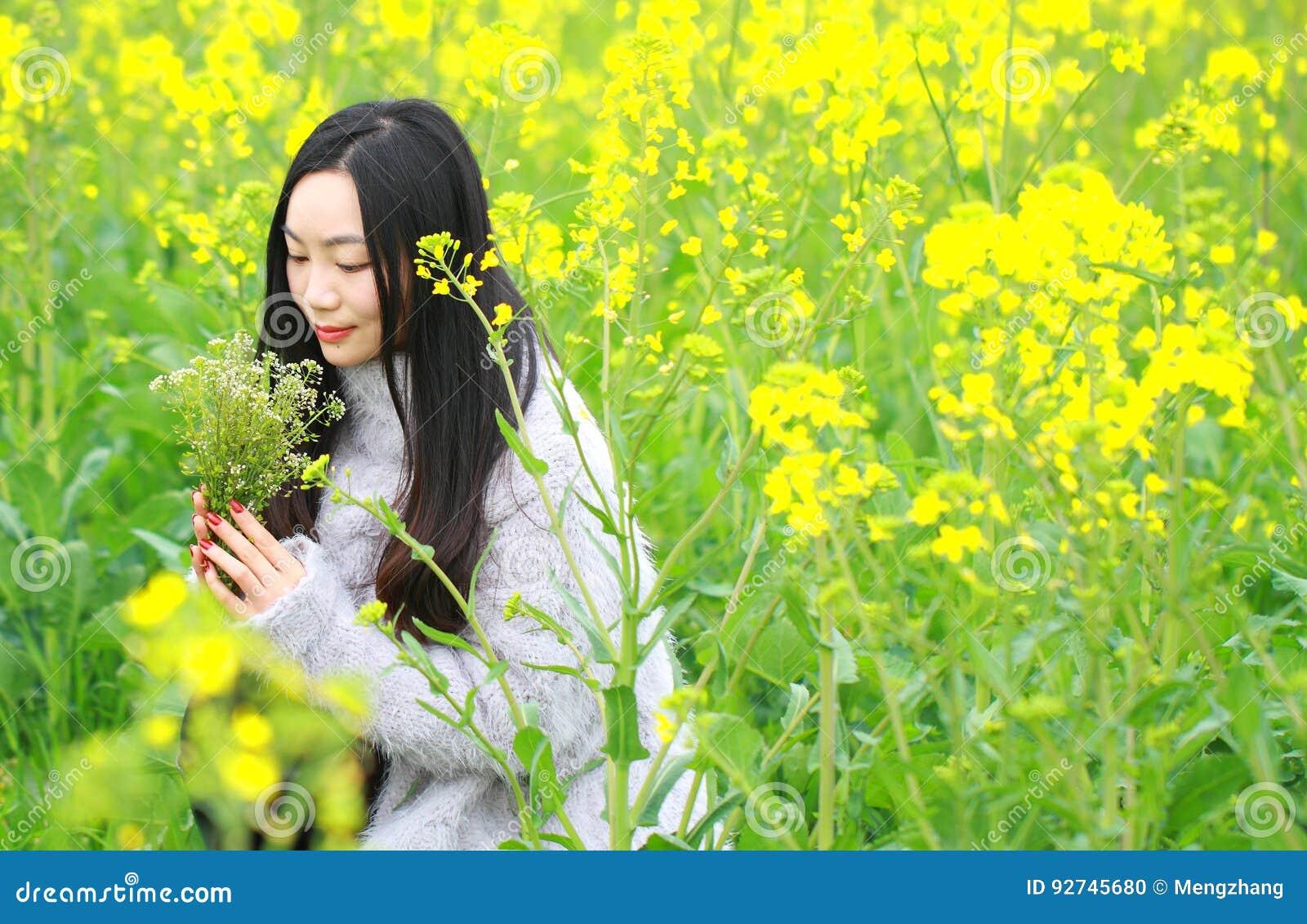 En la primavera temprana hermosa, un soporte de la mujer joven en el medio de las flores amarillas de la violación archivó que es