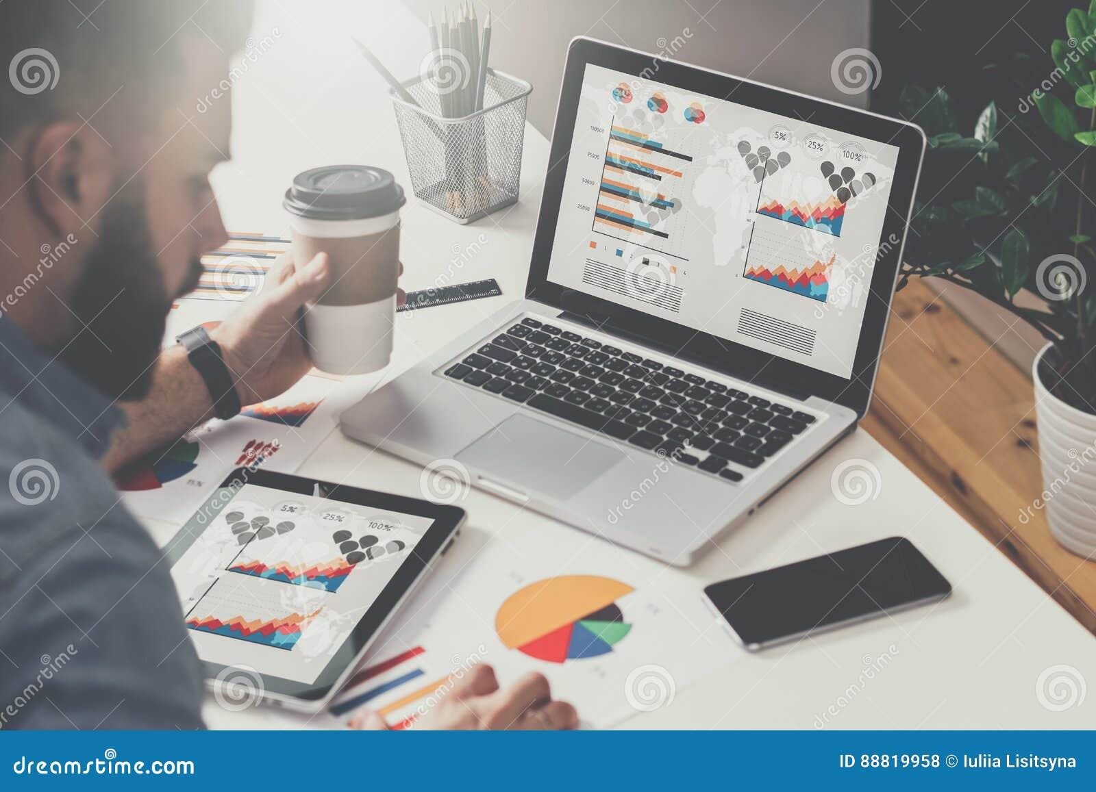 En la tabla es el ordenador portátil y la tableta con los gráficos, los diagramas y las cartas en la pantalla, smartphone, gráfic
