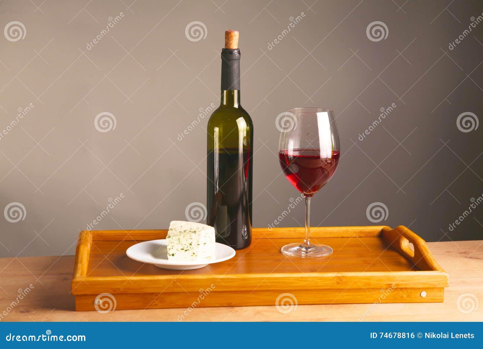 En la tabla una botella de vino y de un vidrio de