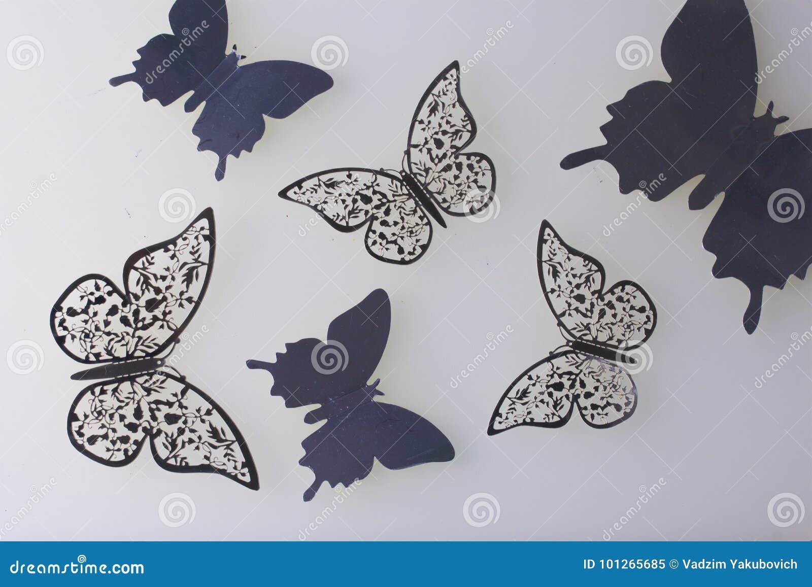 En las decoraciones superficiales blancas de la mentira hechas que de las mariposas cortan de hoja
