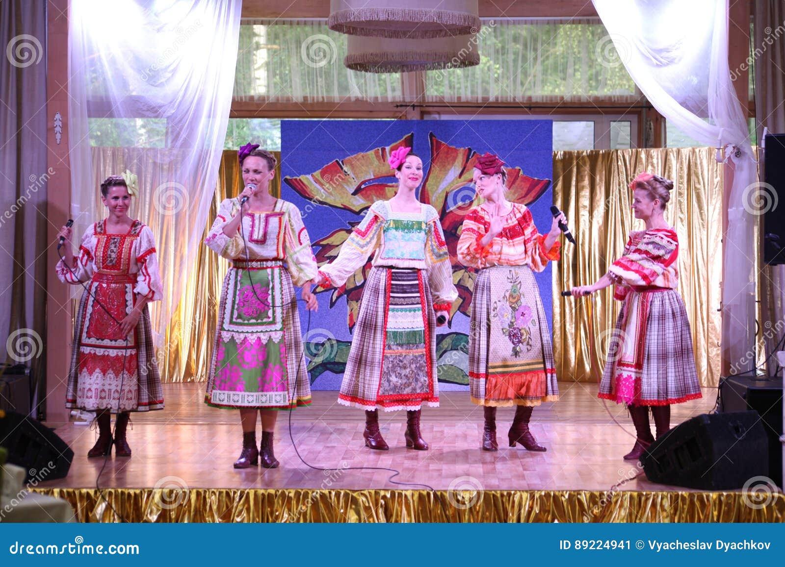 En las muchachas hermosas de la etapa en trajes rusos nacionales, sundresses de los vestidos con el bordado vibrante - grupo de l
