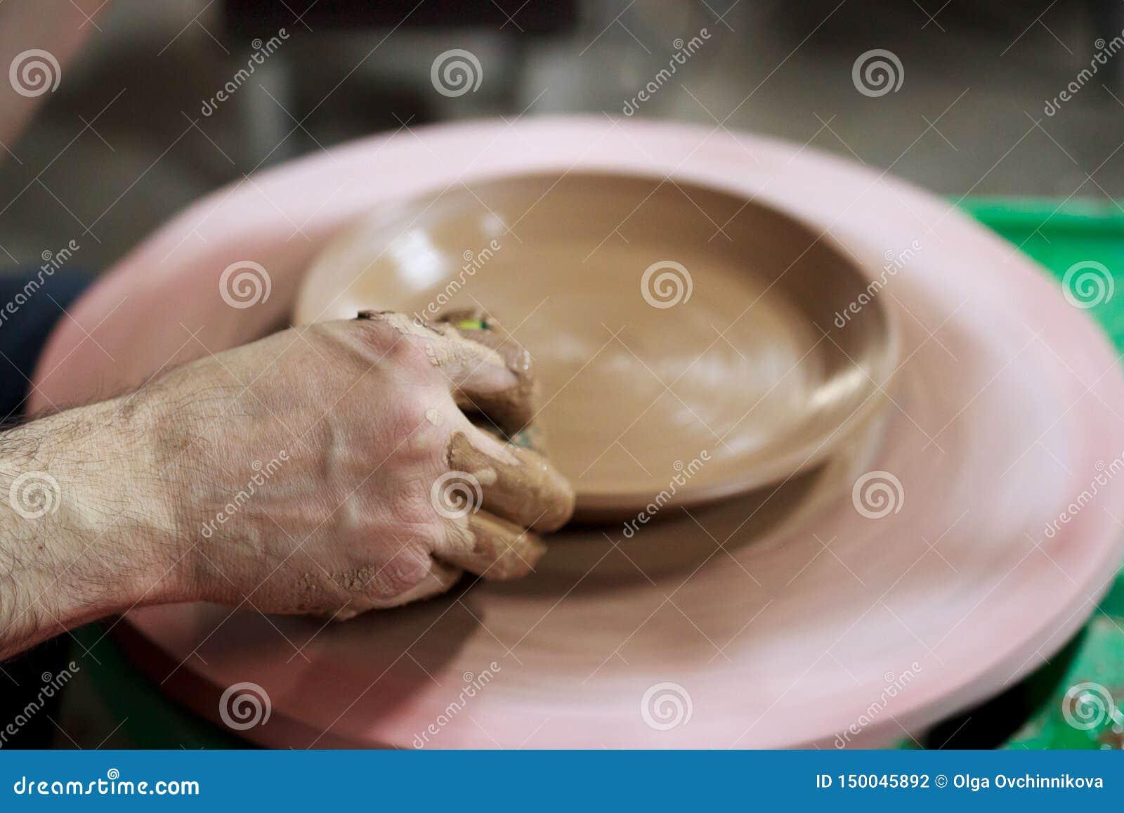 En ledar- ceramist med 13 år av erfarenhet gör plattan från röd lera på keramikers hjul, på ett ark av partikeln