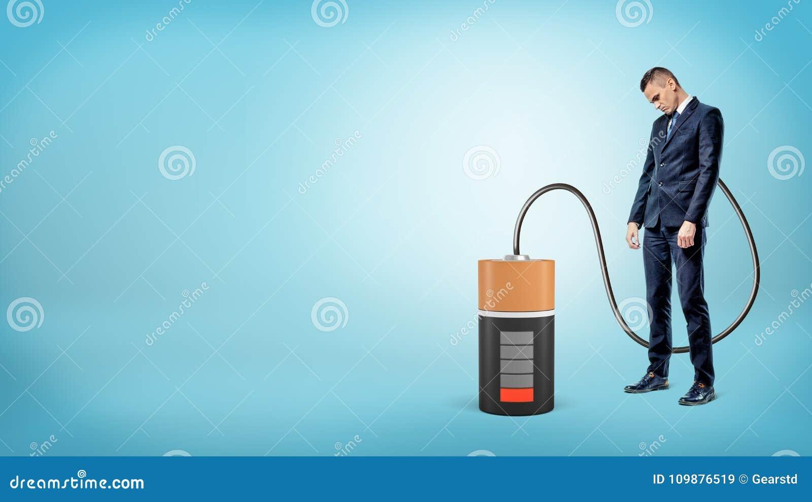En ledsen affärsman med hans huvud står ner förbindelse av kabel till ett stort tomt batteri