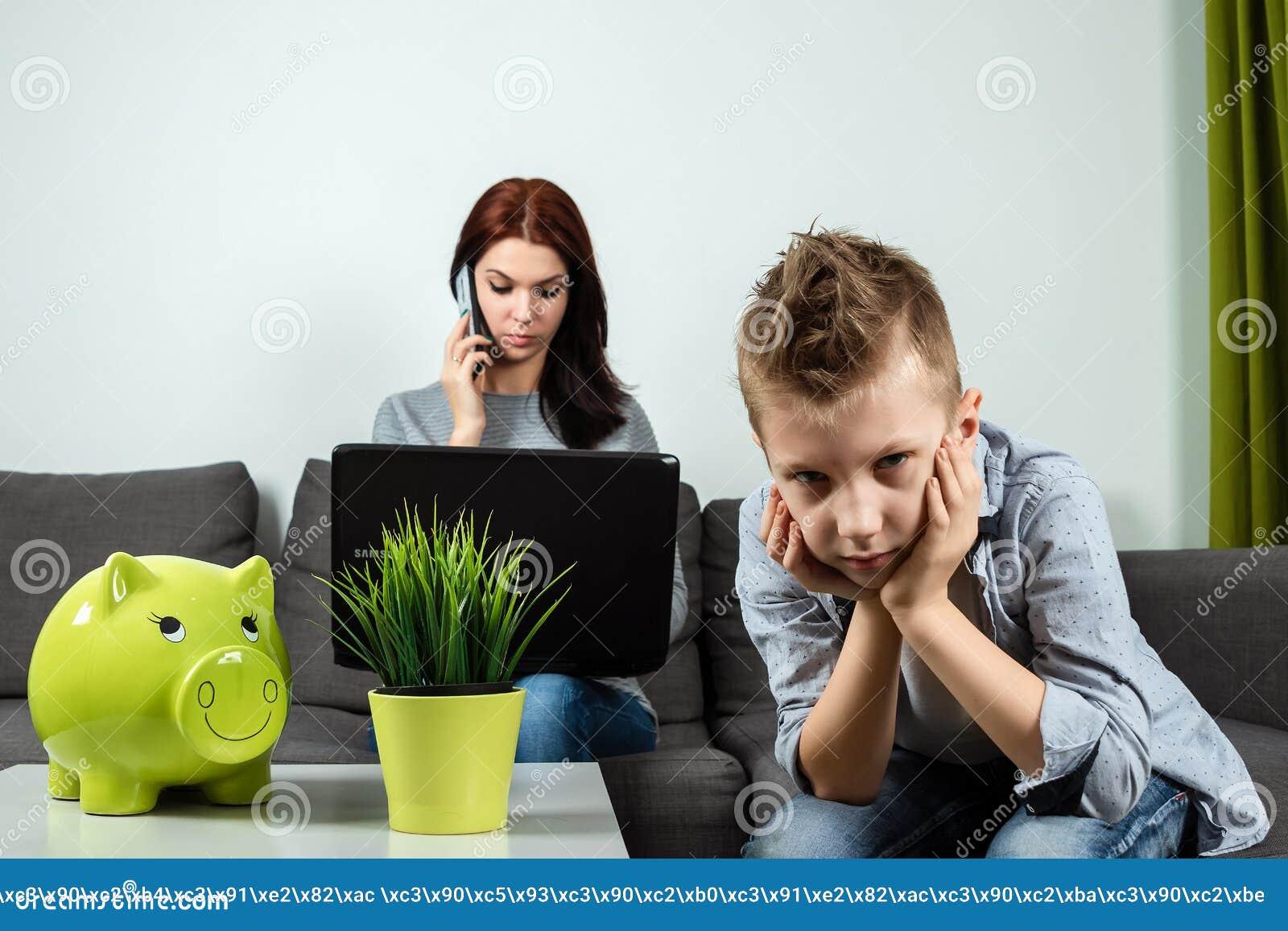 En ledsen pojke ser kameran, medan hans mamma arbetar i bakgrunden hemma Begreppet av tid tillsammans, ensamma barn, arbete
