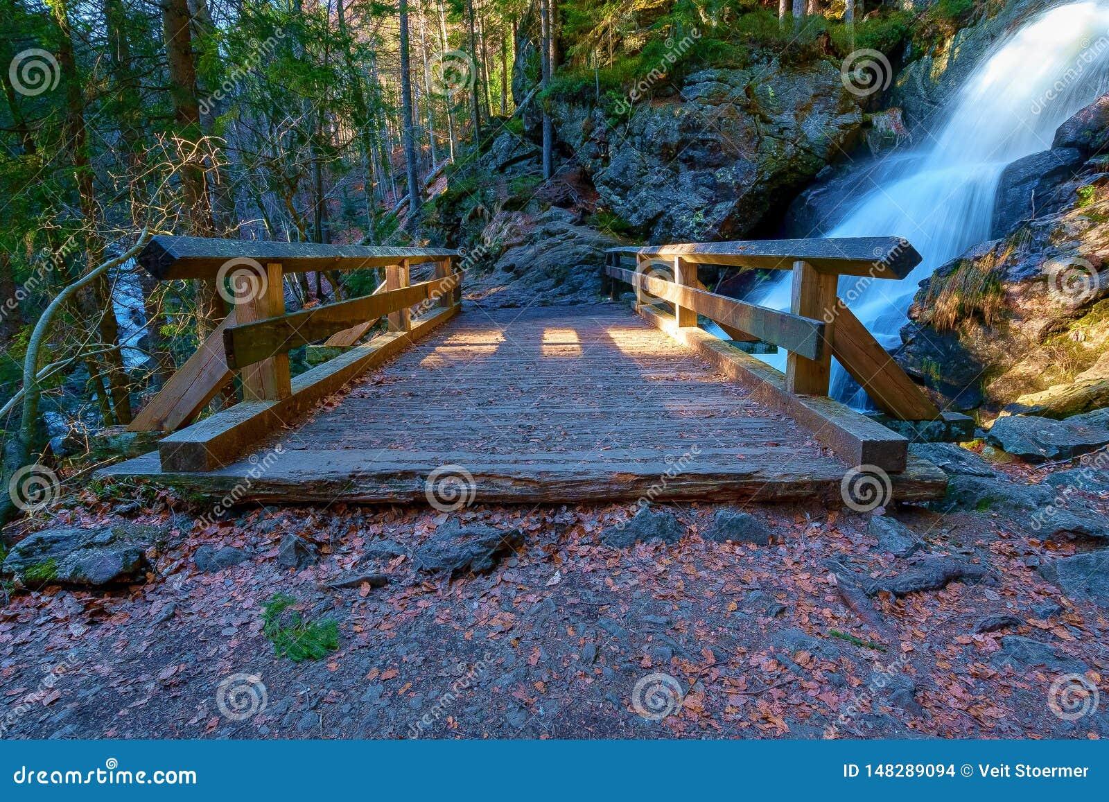 En liten bro framme av en vattenfall