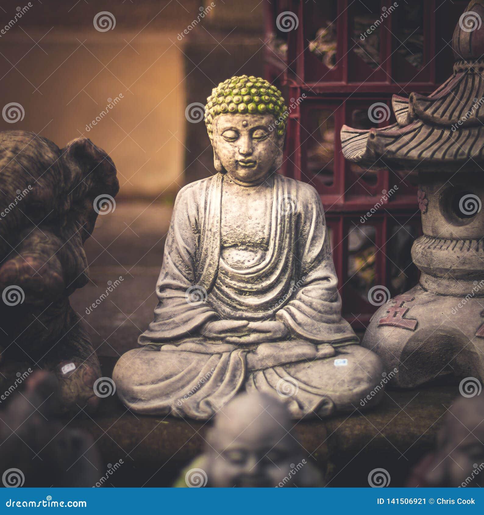 En liten liten Buddhastaty som döljas bort i en marknad