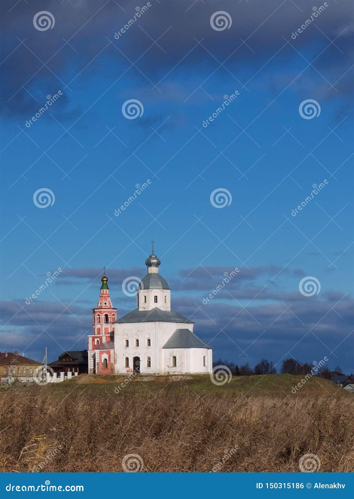 En liten ortodox kyrka på en kulle mot en blå himmel