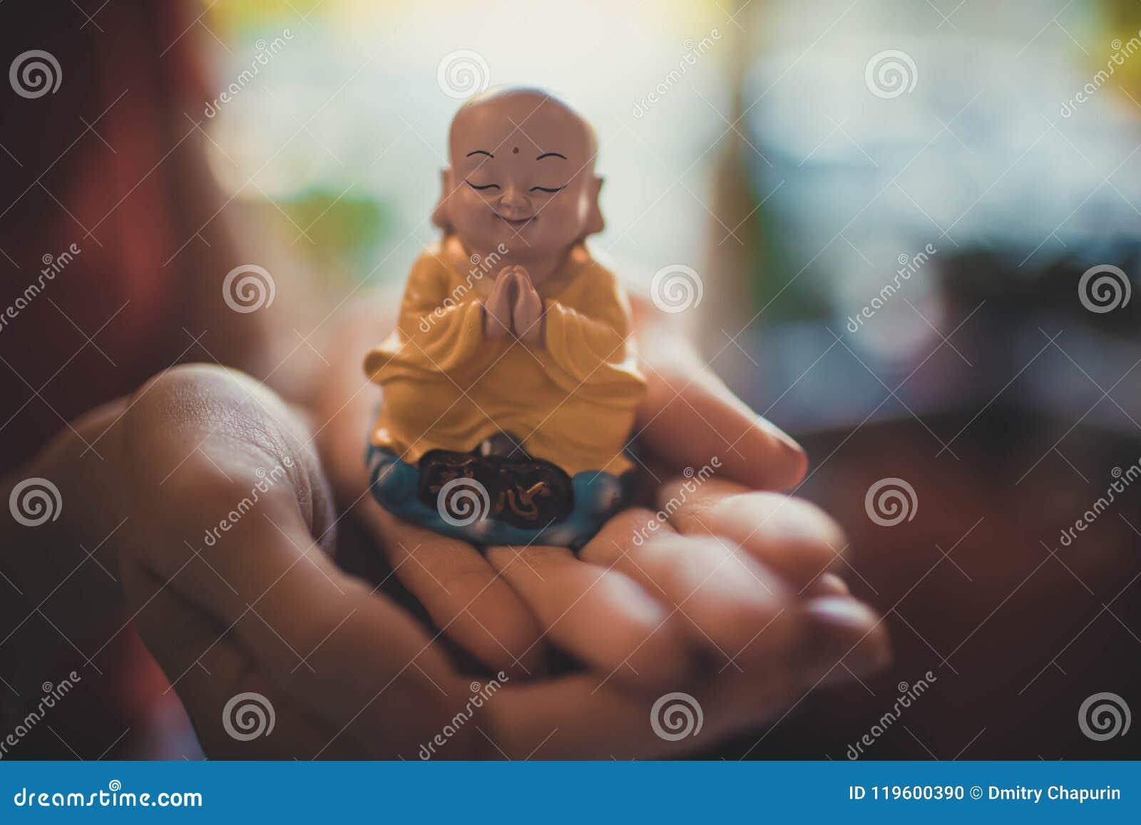 En liten staty av Buddha i händerna av en kvinna