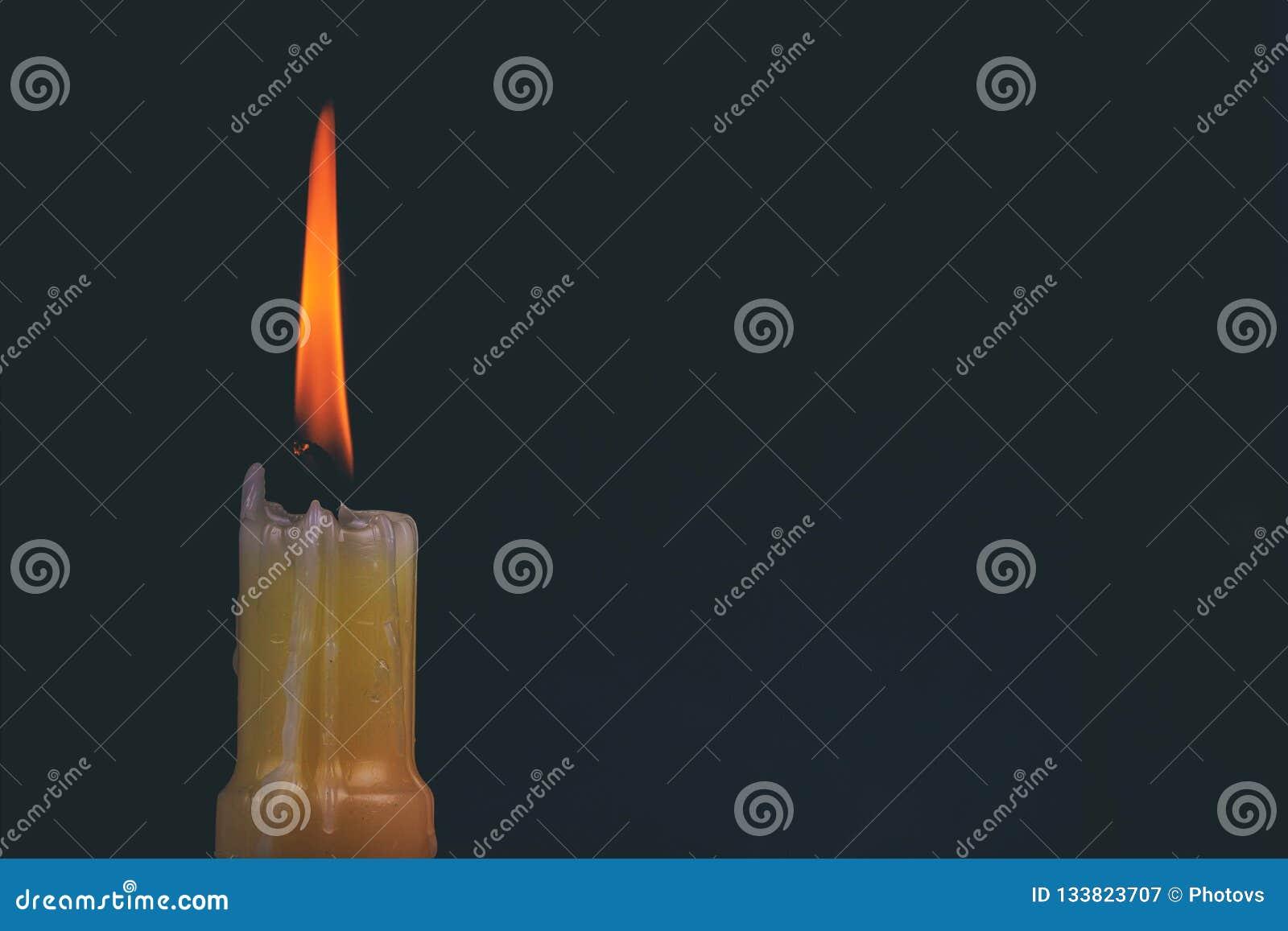En ljus minnes- stearinljus som ljust bränner i den svarta bakgrunden