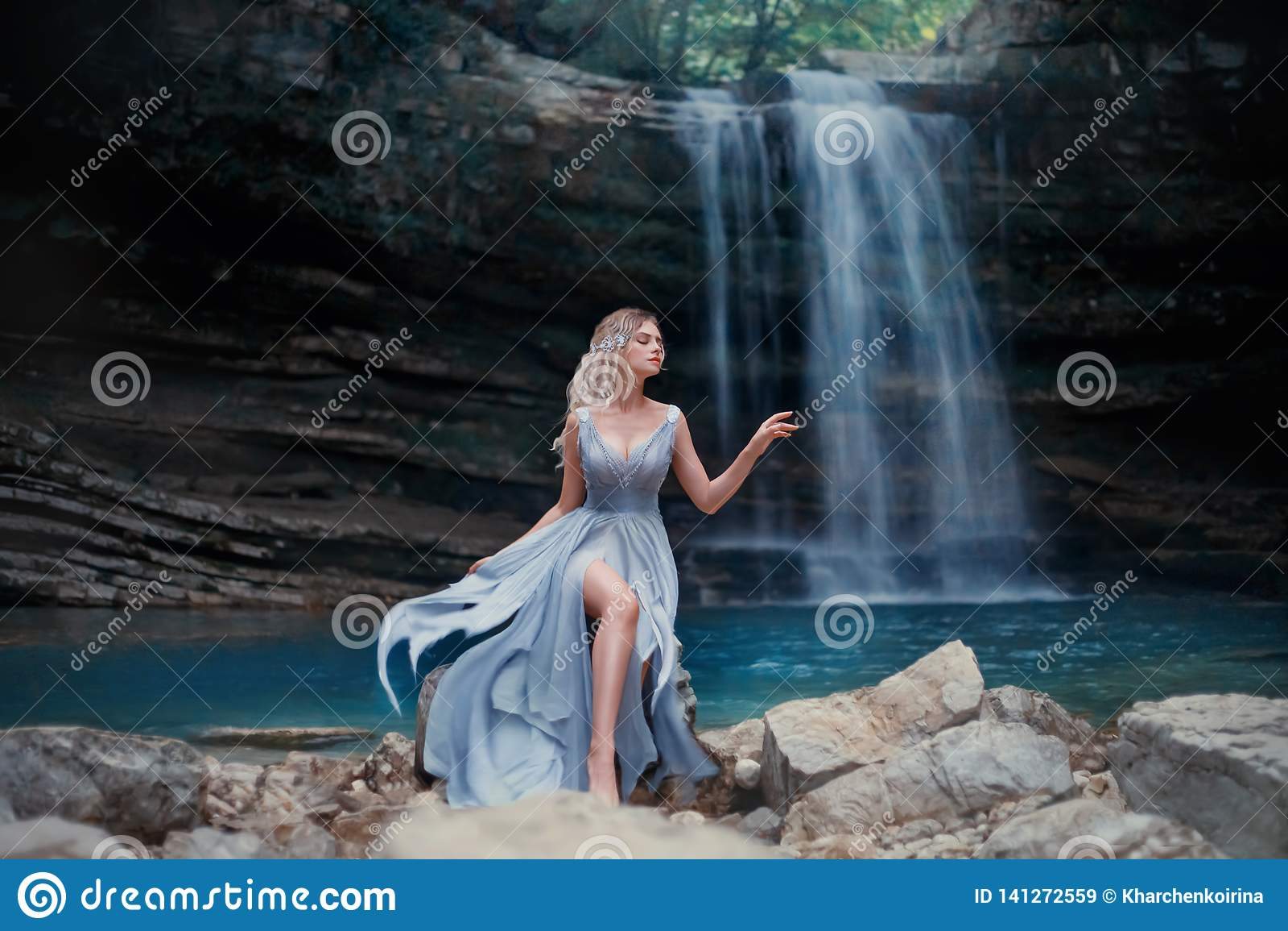 En lockig blond flicka i en lyxig blå klänning sitter på vita stenar mot bakgrunden av ett sagolikt landskap Flod