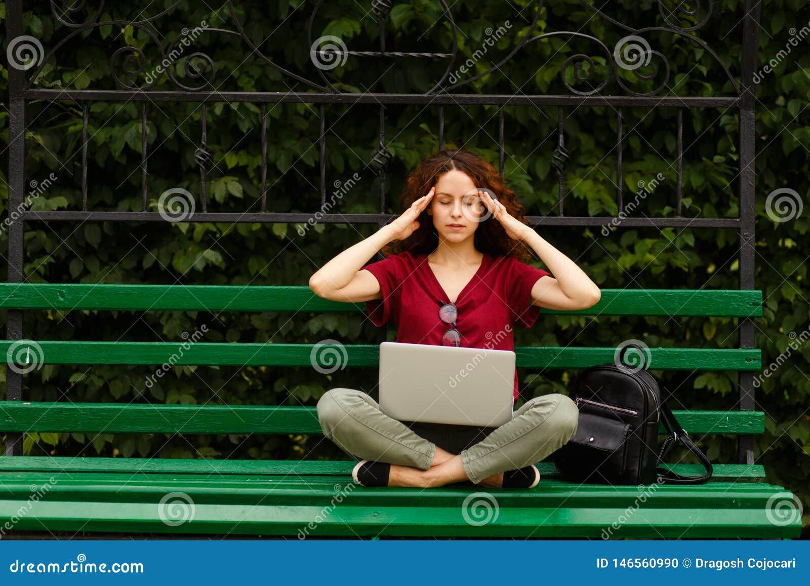En lockig ung kvinna med stängda ögon som arbetar på en bärbar dator som placeras på en grön bänk parkerar in, touche hennes temp