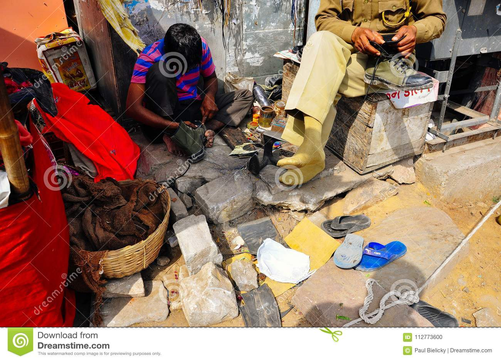 En lokal reparerar en sko för man` s i Jaipur, Indien