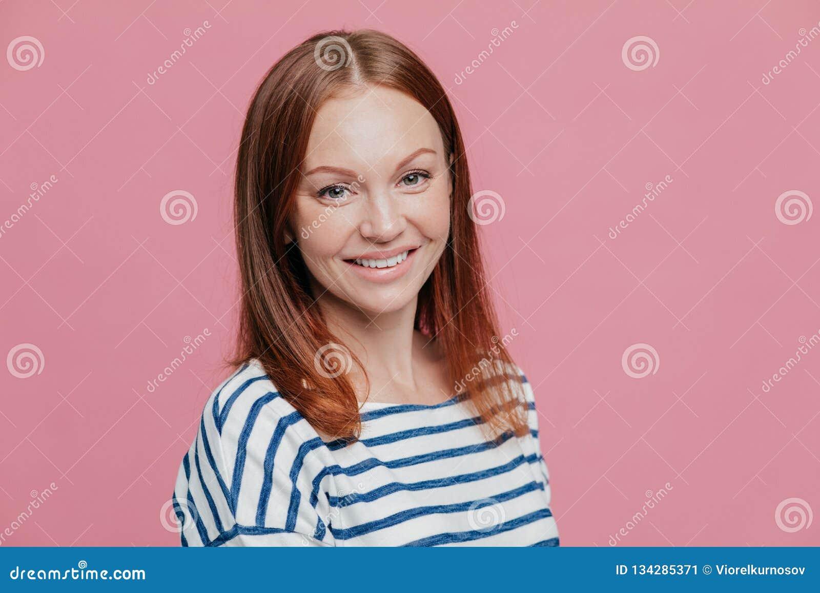 En longueur tiré de la femme d une chevelure brune heureuse agréable à regarder avec les cheveux droits, peau saine, sourire agré