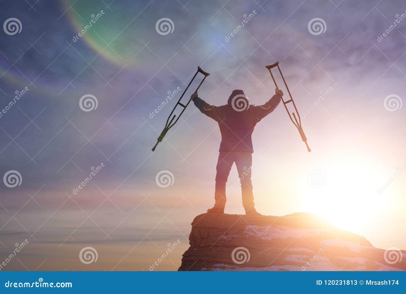 En lycklig man överst av ett berg med kryckor och att lyfta upp hans händer, mitt emot en dramatisk himmel på gryning