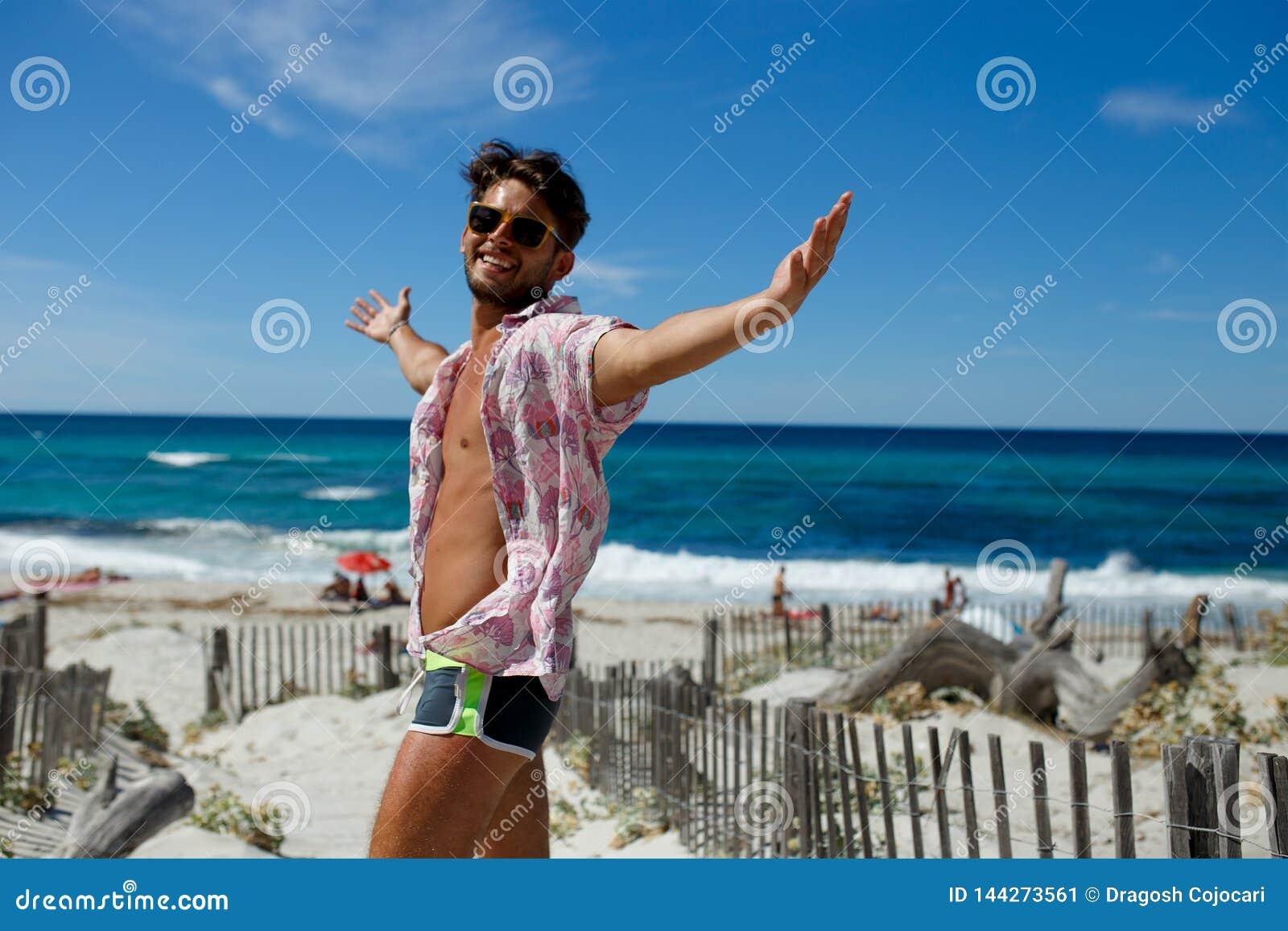 En lycklig sexig ung man som poserar med lyftta händer på stranden, bär i en swimwear, skjorta, på strandbakgrund